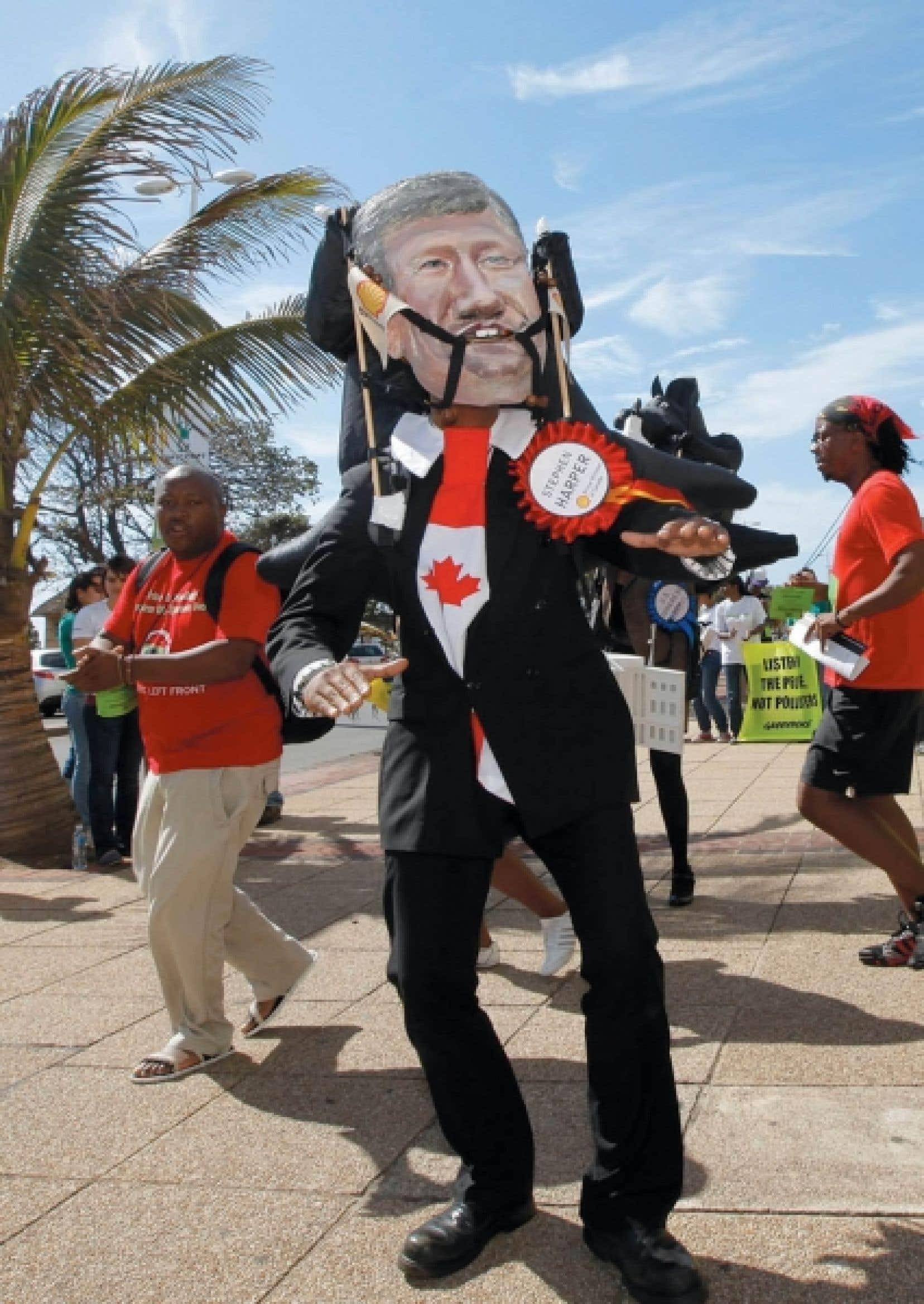 Un manifestant portant un masque à l'effigie du premier ministre Harper dénonce la position du Canada face au Protocole de Kyoto, à l'occasion de la conférence de Durban sur les changements climatiques, en décembre dernier.<br />