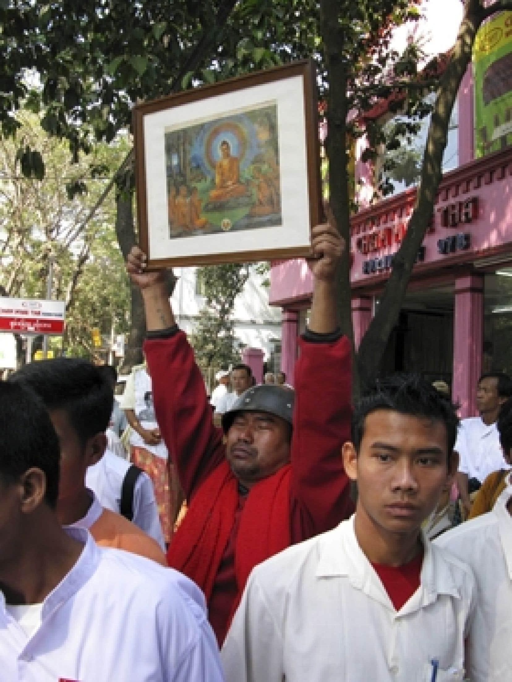 Un casque militaire et une image de Bouddha: à l'instar de ce manifestant, ils étaient 350 à protester, hier dans les rues de la capitale, contre le régime militaire du Myanmar.