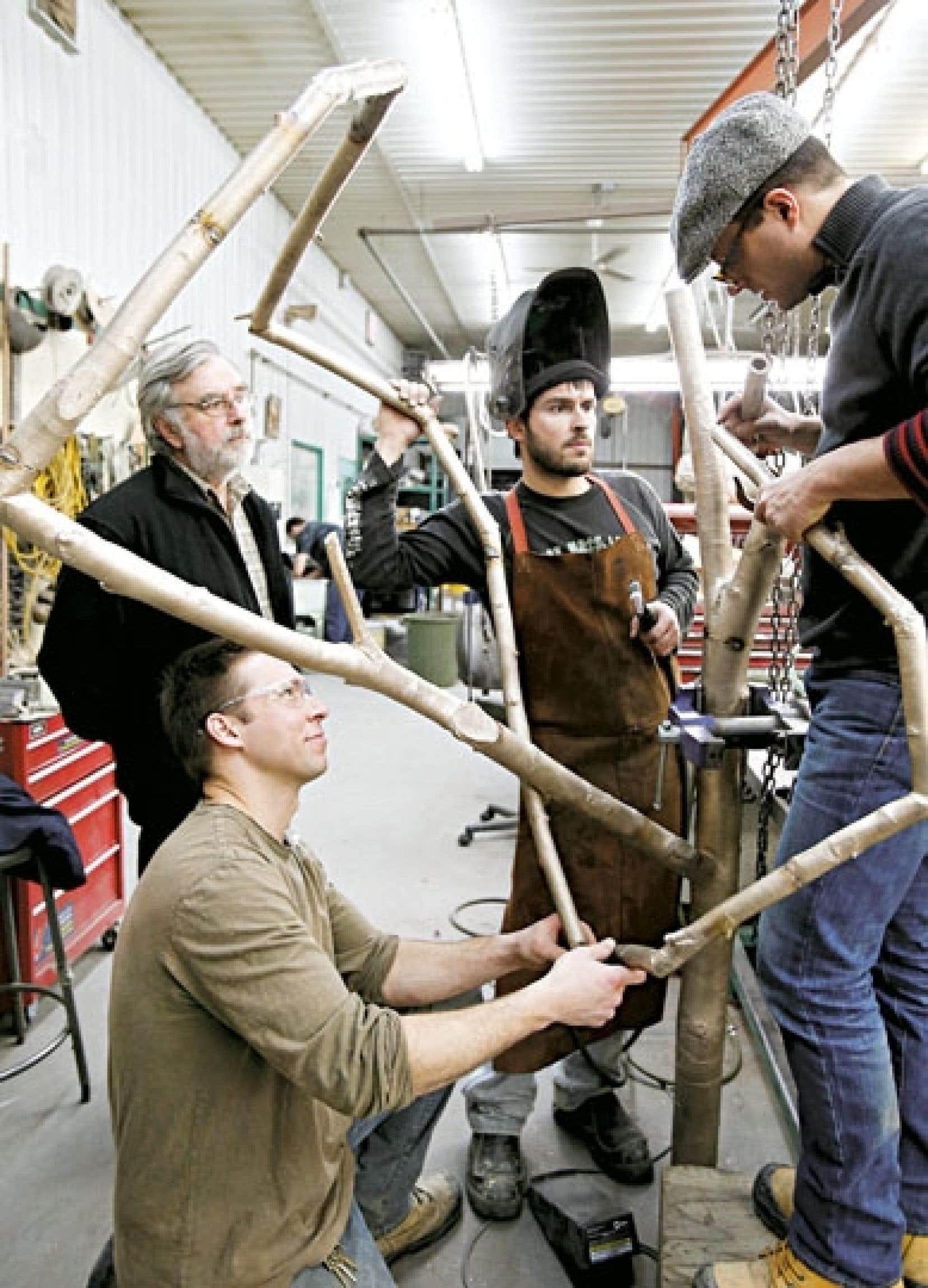 L'artiste Marc Dulude (à droite) au travail avec le père et les fils Gagnon.