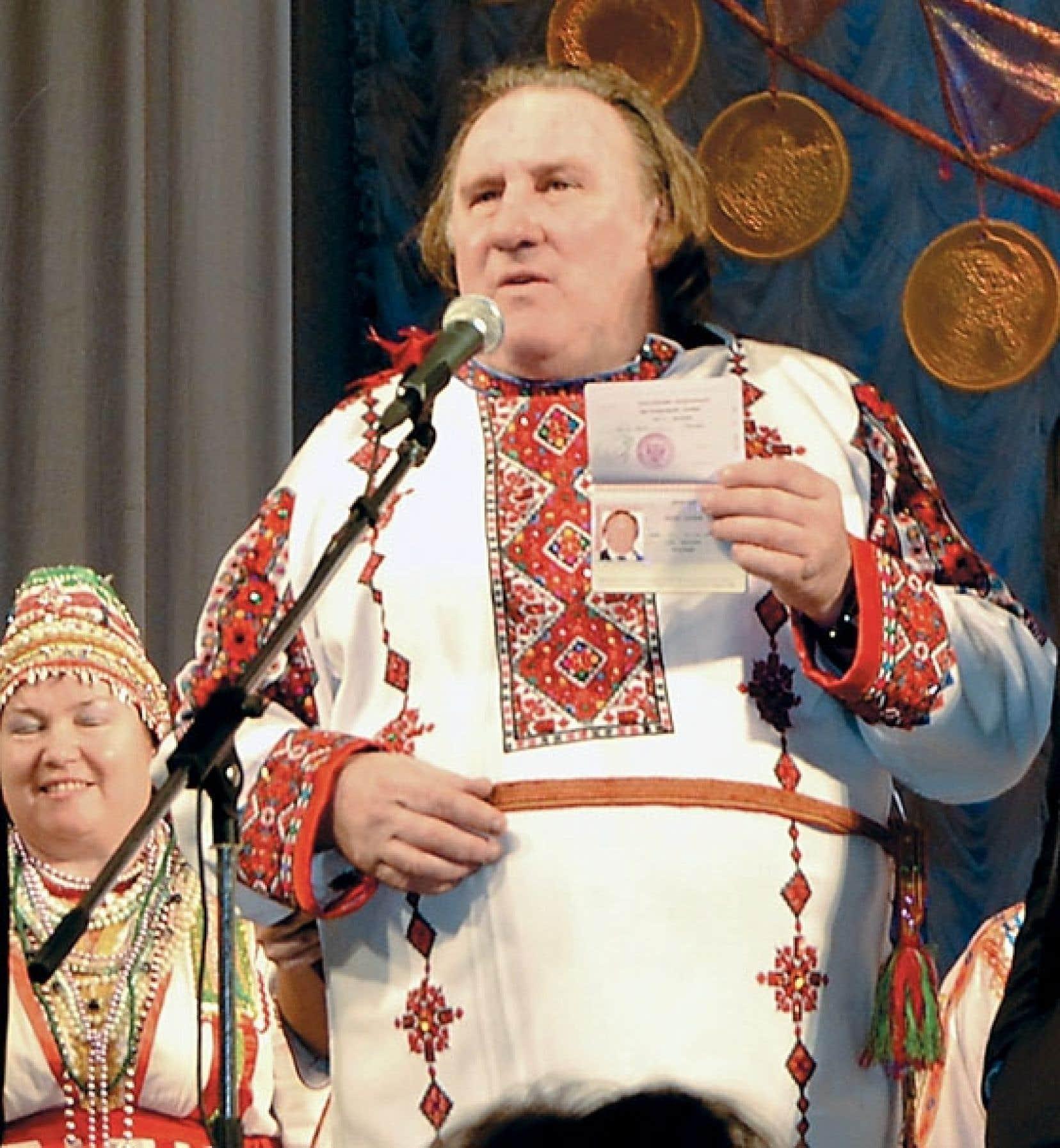 Gérard Depardieu pose avec son nouveau passeport russe sur une scène de théâtre, vêtu d'un costume folklorique, suite à son arrivée dans la ville de Saransk, à environ 700 km de Moscou.