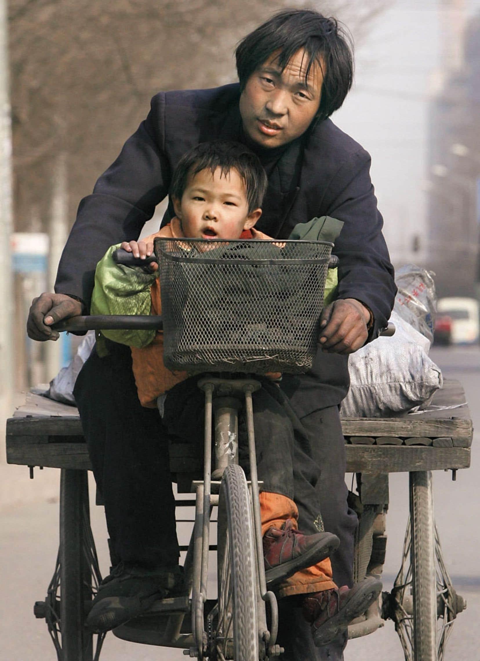 Venu de la campagne en espérant améliorer son sort et celui de sa famille, cet homme parcourt les rues de Pékin sur son tricycle, accompagné de son enfant.