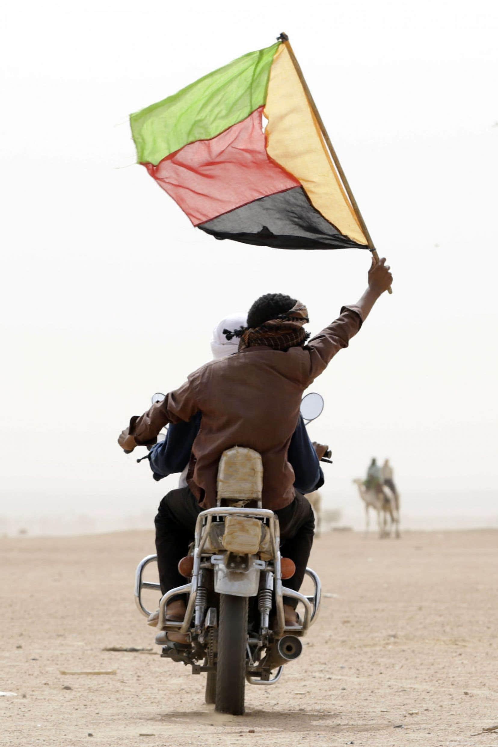 Un touareg rebelle brandit le drapeau du Mouvement national pour la libération de l'Azawad, ce dimanche, à Kidal.