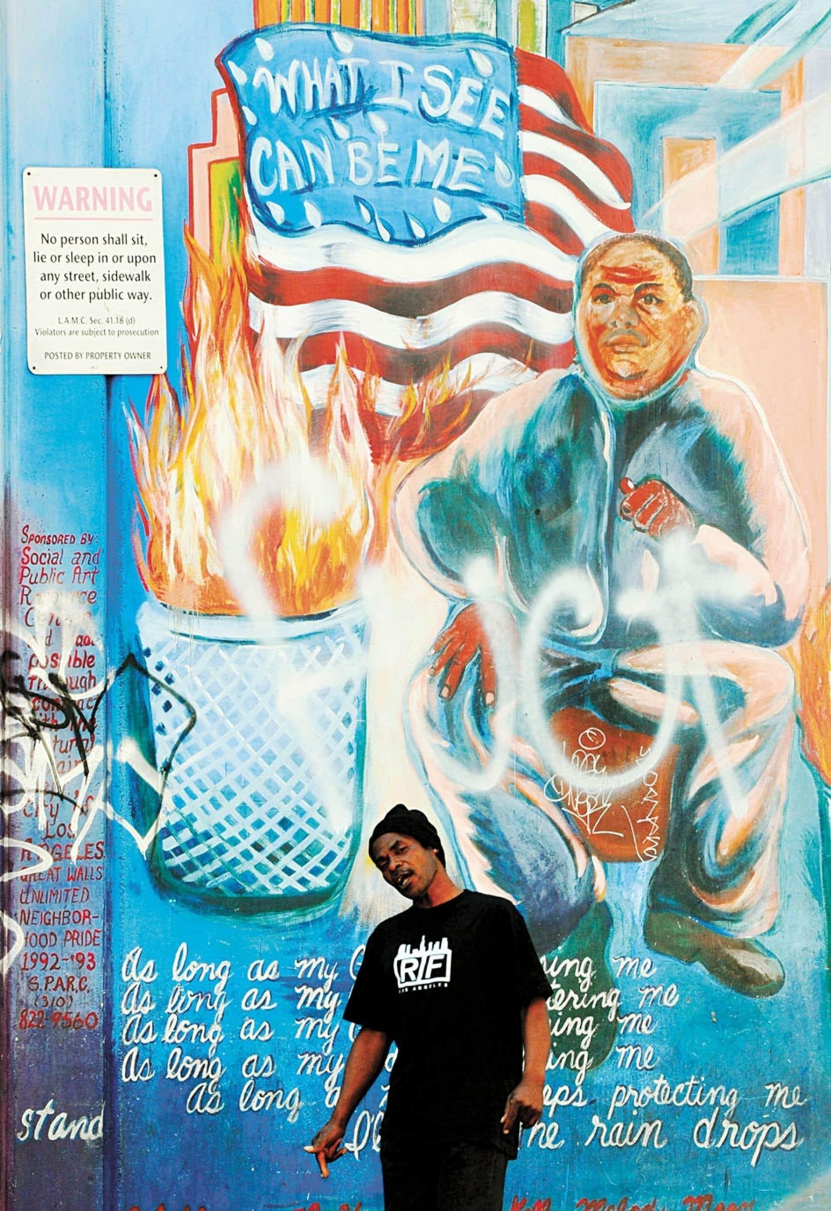 À Los Angeles, un homme sans emploi passe devant un immense graffiti. La communauté afro-américaine souffre davantage du chômage que l'ensemble des Américains.