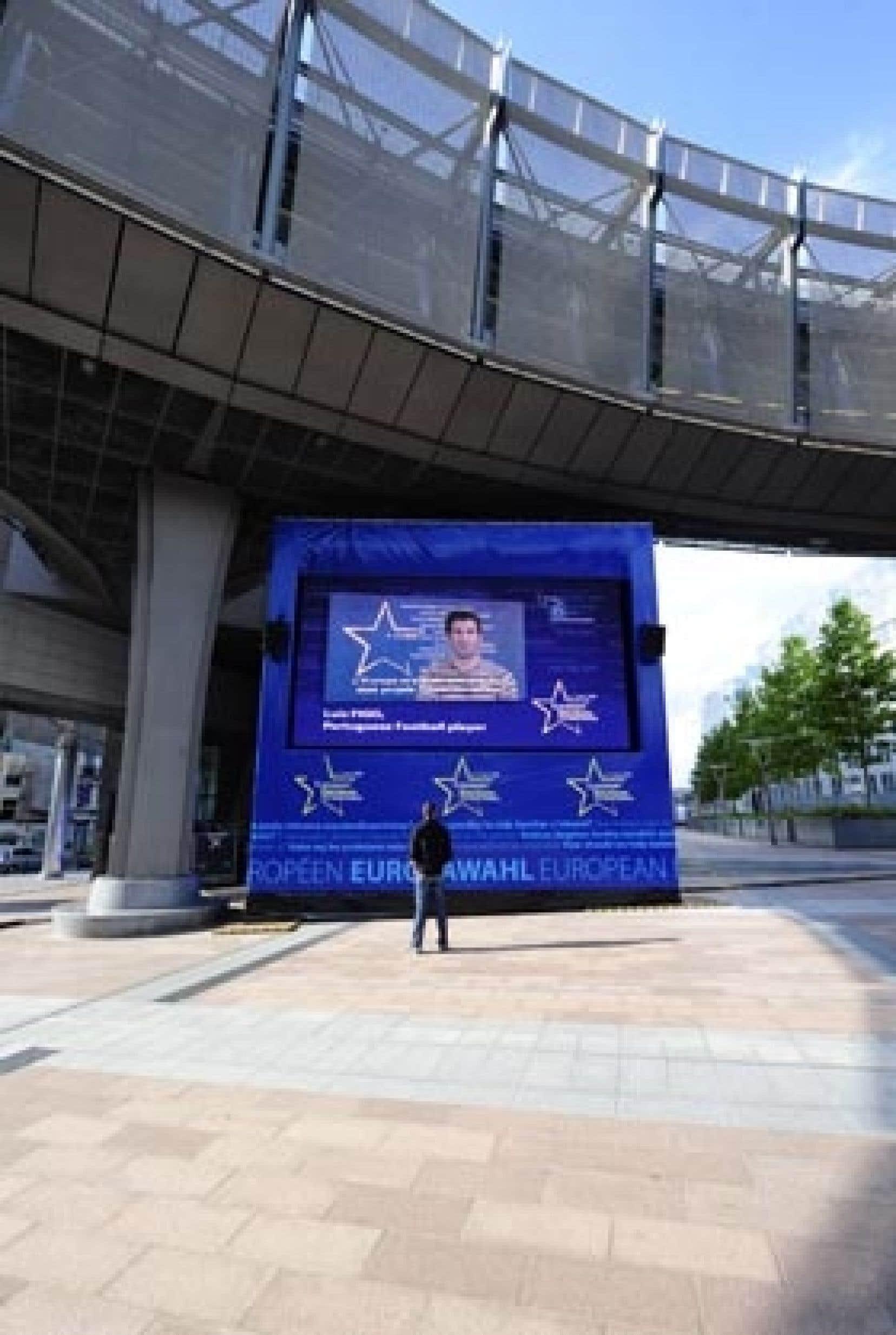 Un homme suit les élections européennes sur un écran installé en bordure du Parlement européen, à Bruxelles.