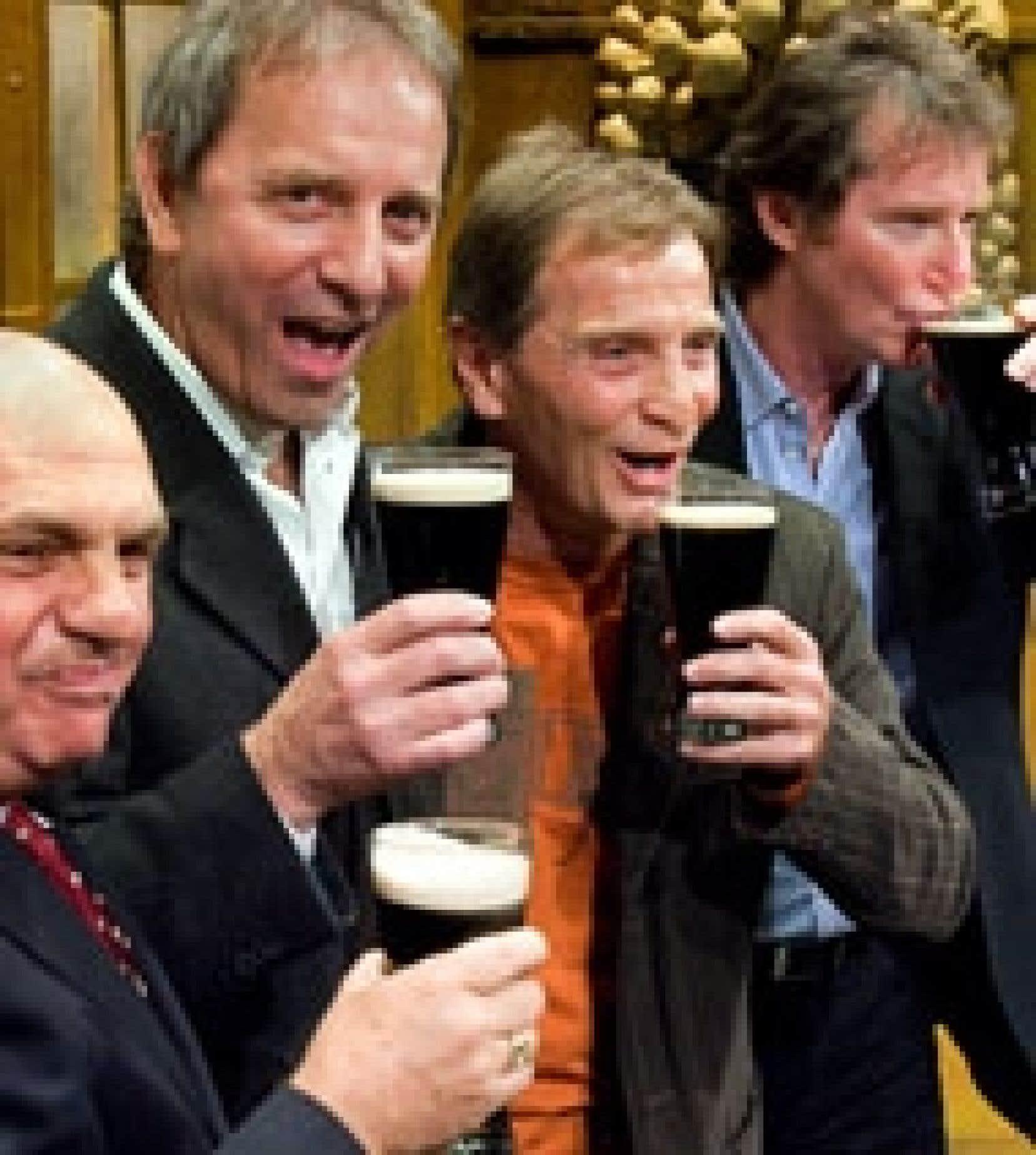 Michel Côté, Michel Gauthier et Marc Messier buvaient de la bière Guinness en compagnie de Claude Charron (à gauche) pour célébrer leur mention dans le livre des records Guinness.
