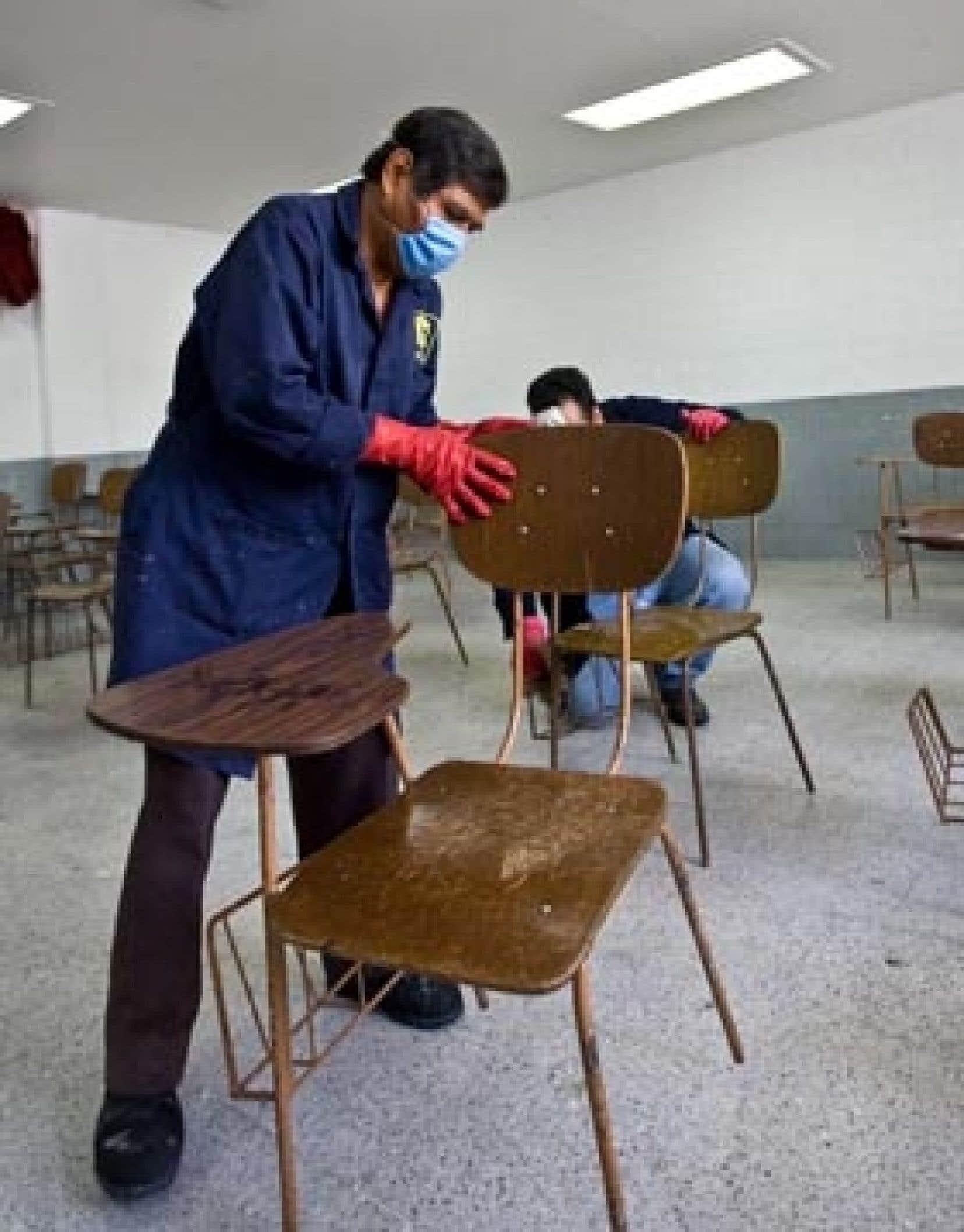 Des employés d'une école mexicaine désinfectent les tables et les chaises d'une classe en prévision du retour des élèves.
