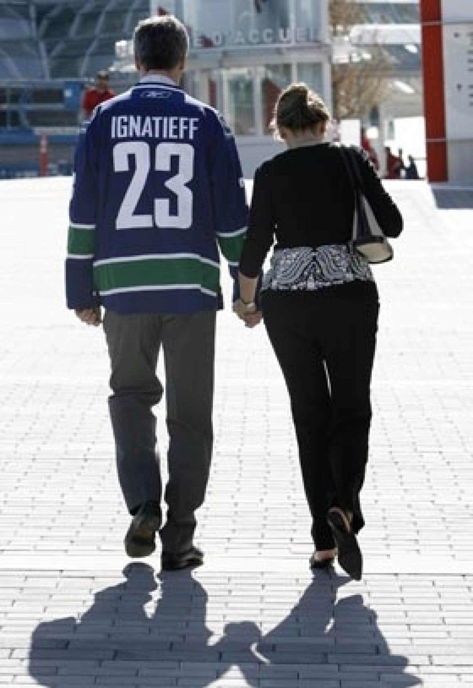 Vêtu d'un chandail des Canucks de Vancouver, Michael Ignatieff marche avec sa conjointe.