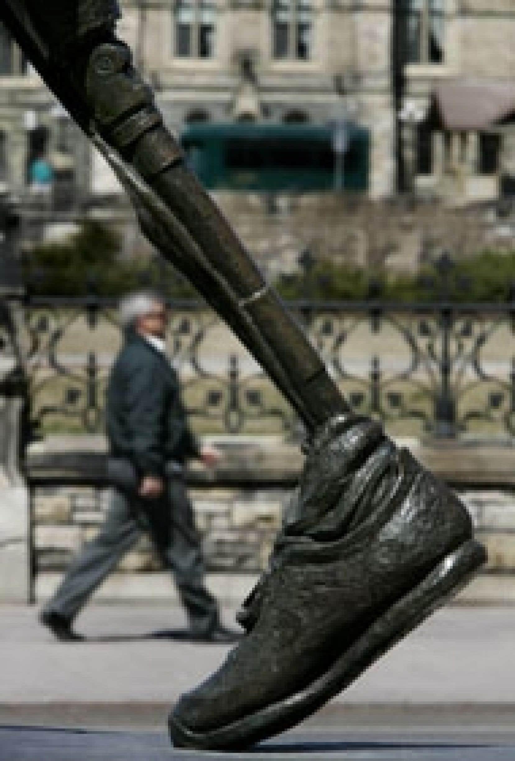 Un homme marche devant une statue édifiée en l'honneur de Terry Fox.