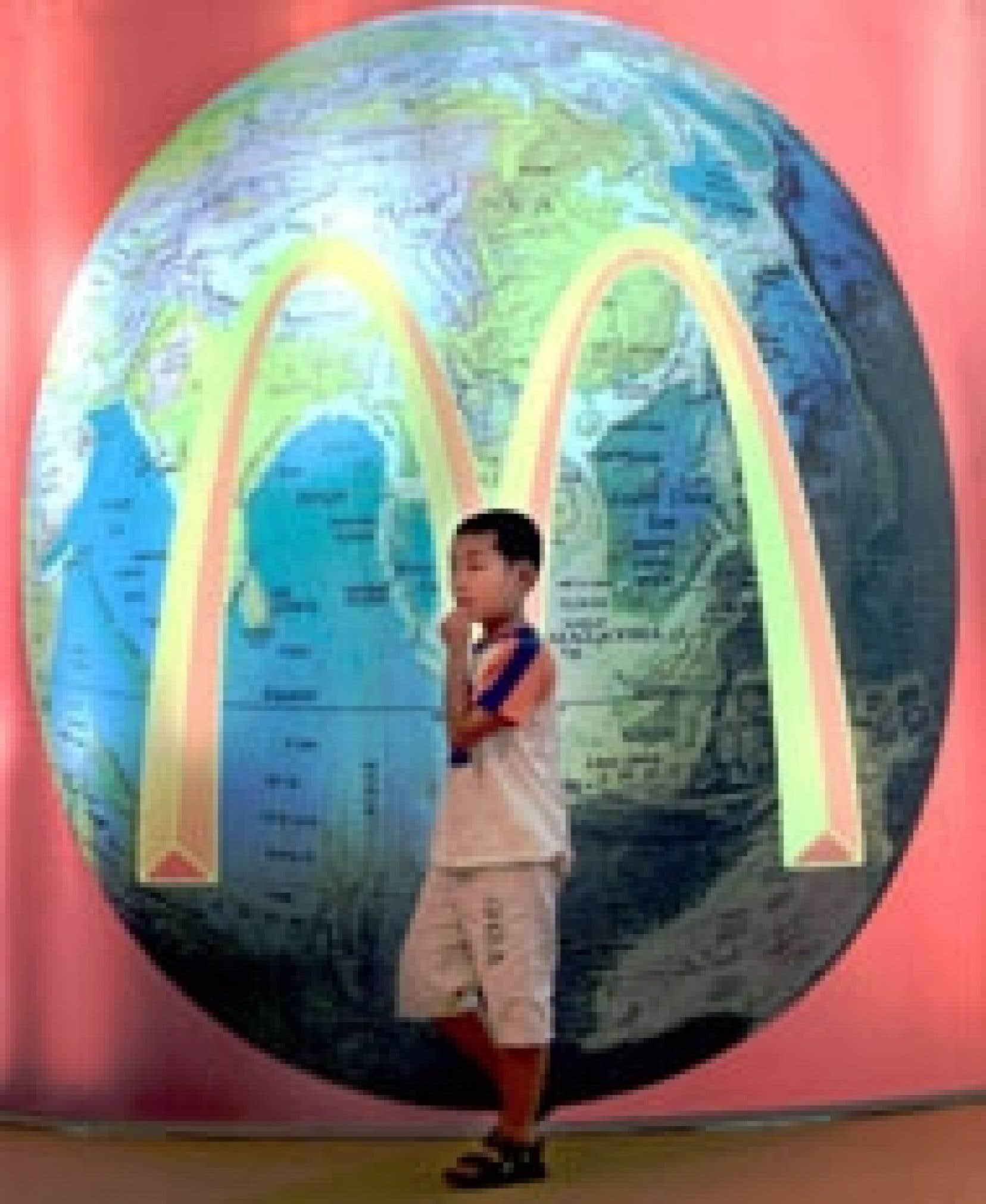 Un jeune Chinois devant une affiche soulignant l'ouverture d'un McDonald à Pékin. En janvier dernier McDonald's dévoilait un bénéfice net de près de 2,3 milliards $US. L'action, tombée jusqu'à 12,50 $US en mars 2003, dépasse désormais