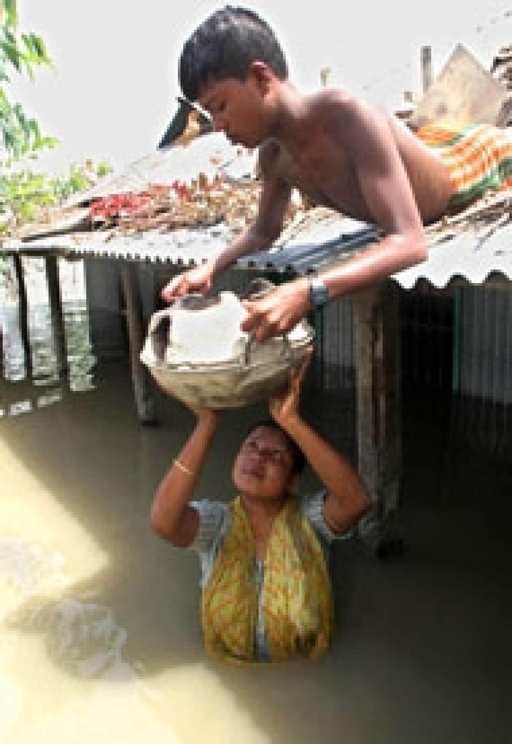 Quand la maison est inondée et qu'il faut se nourrir coûte que coûte, quoi de plus vital que de sauver la marmite et tout ce qui permet de cuisiner, comme le font ici ces deux habitants du Bangladesh.