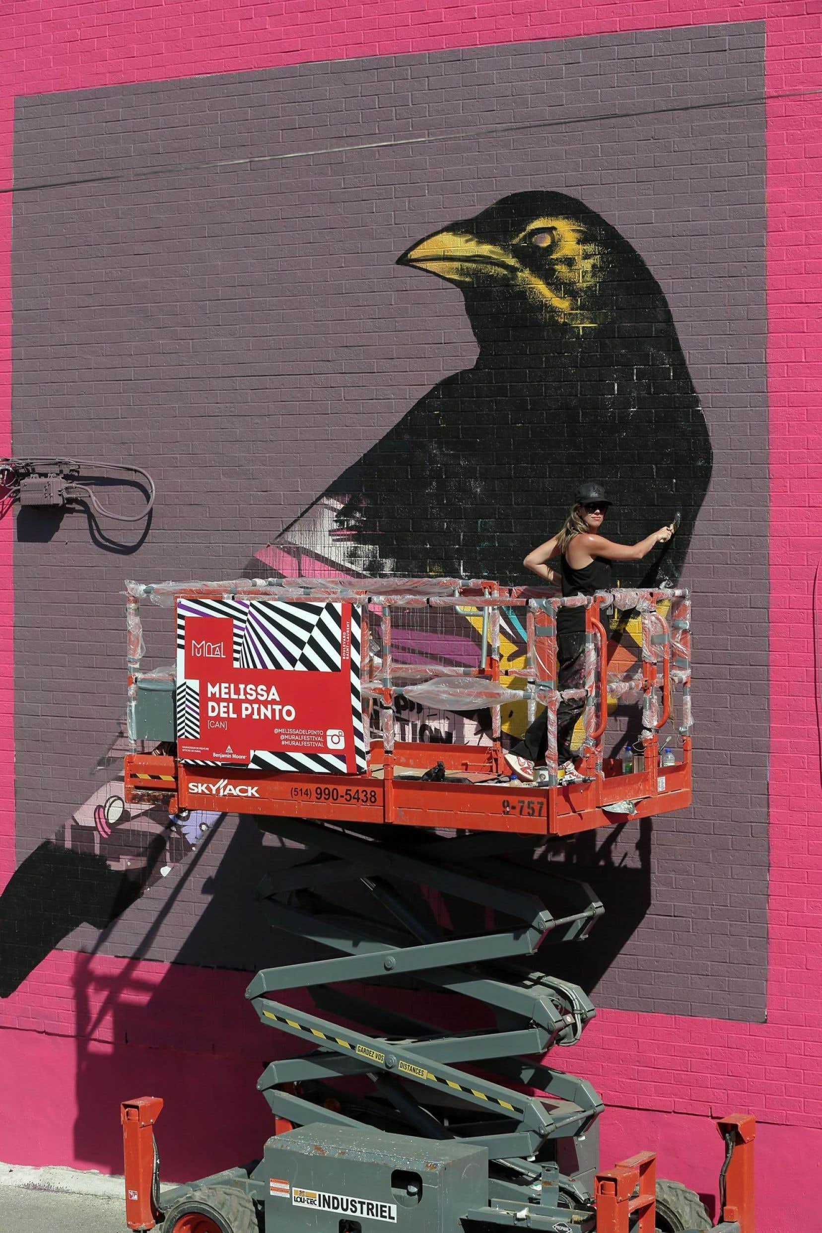 L'artiste montréalaise Melissa del Pinto peint une corneille géante pour le festival d'art public MURAL, qui se tient jusqu'au 14juin. Le boulevard Saint-Laurent est fait piéton pour l'occasion.