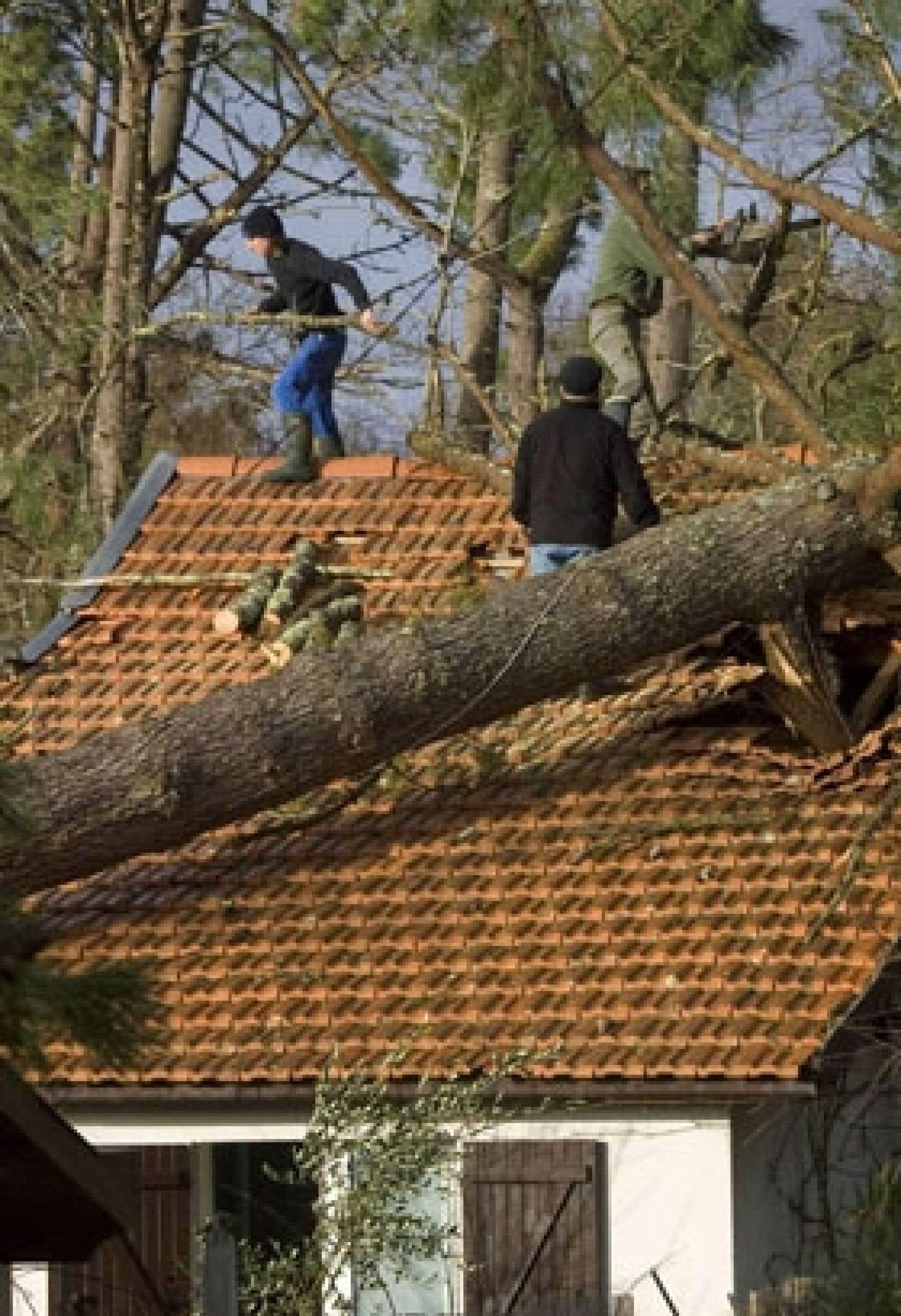Des ouvriers s'affairent à enlever les branches d'un arbre tombé sur le toit en tuiles d'une maison de Cap-Ferret, dans le sud-ouest de la France, où les vents ont atteint jusqu'à 180 km/h.