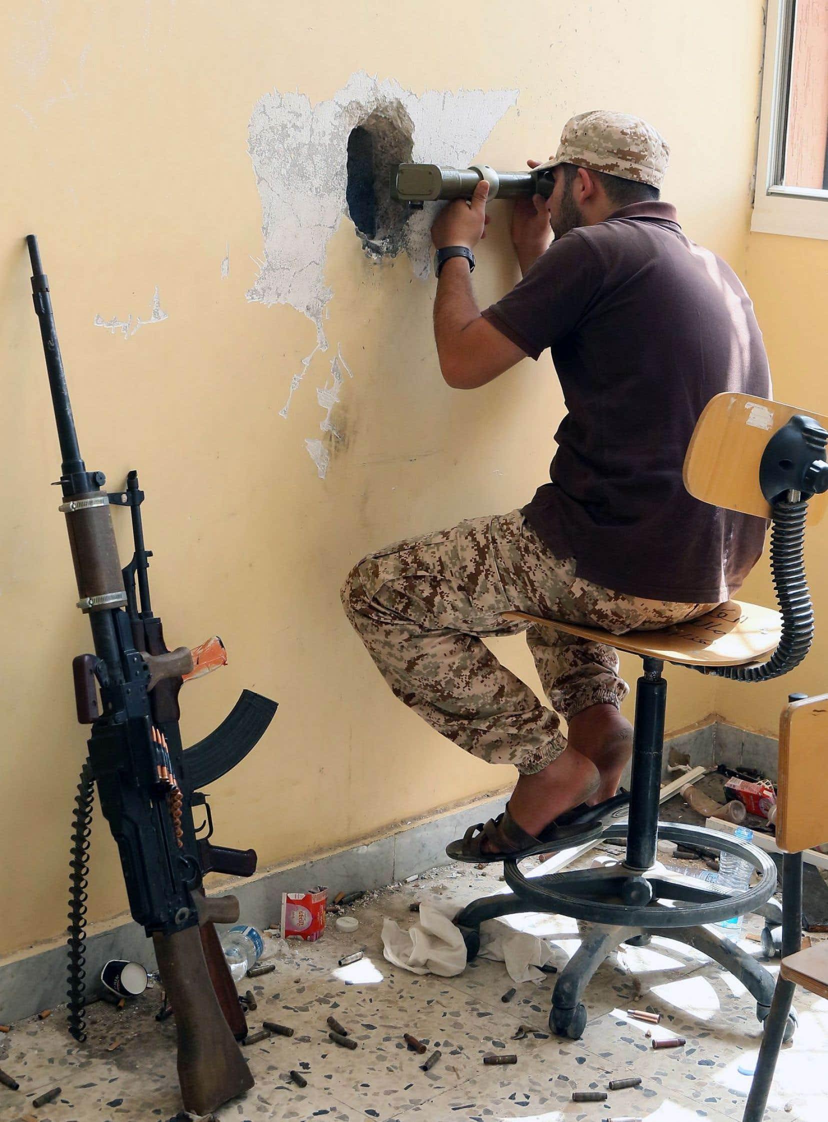 Un membre des forces loyales de la Libye regarde dans un périscope la ligne de front de la ville de Syrte, durant l'opération menée pour éradiquer le groupe État islamique de la ville.