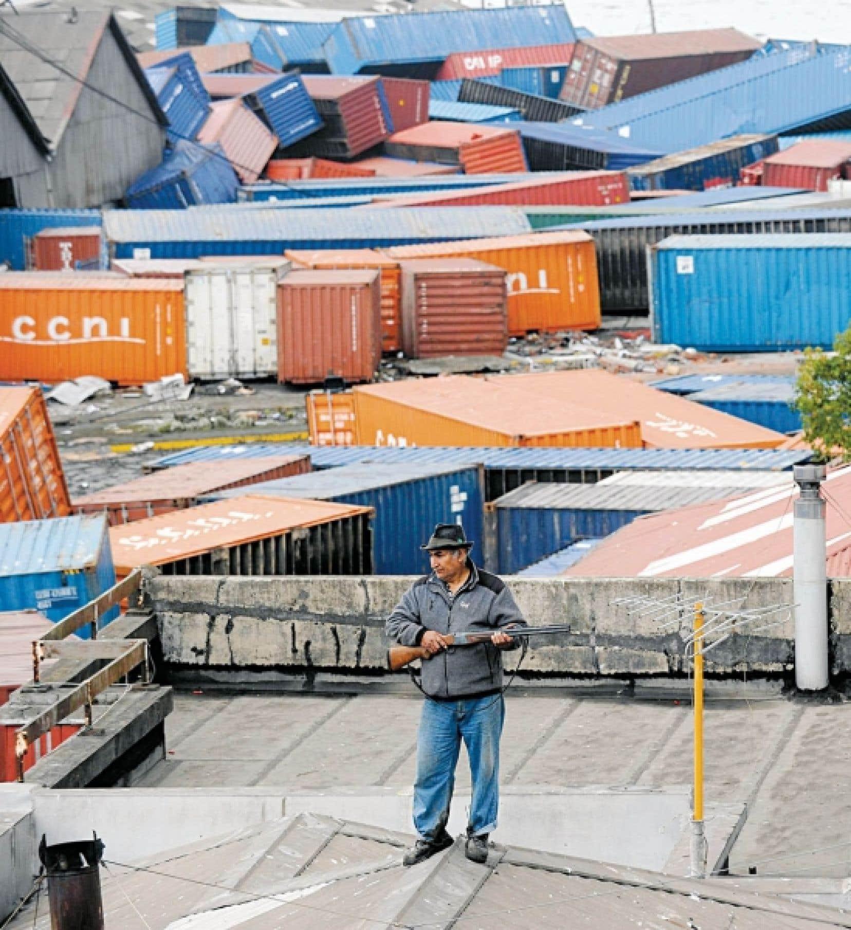 Un homme armé fait le guet sur le toit. Autour de lui sont éparpillés des conteneurs que le tsunami a entraînés sur son passage après le tremblement de terre d'une magnitude de 8,8 au Chili. Appelée en renfort, l'armée tente de rétablir le calme alors que les commerces sont pillés dans les zones sinistrées.