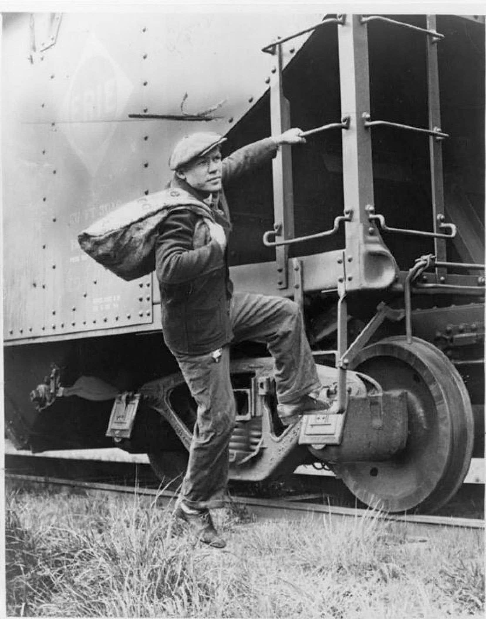 Lou Ambers, sac de voyage à l'épaule, s'accrochant à l'échelle d'un train en 1935