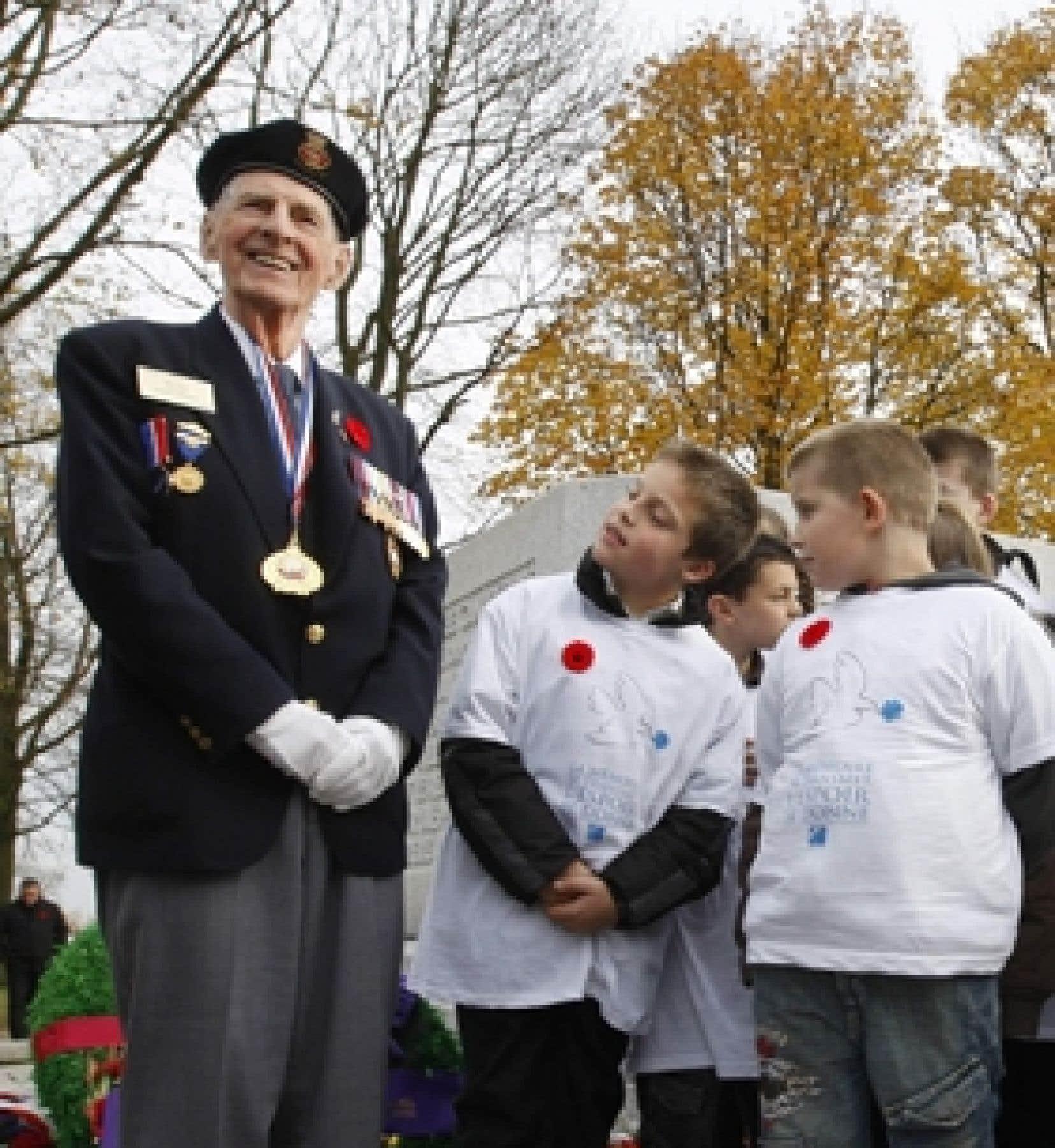 Des enfants regardent les médailles d'un vétéran canadien, Phil Etter, à l'occasion d'une cérémonie qui se déroulait à Le Quesnel, en France, hier.