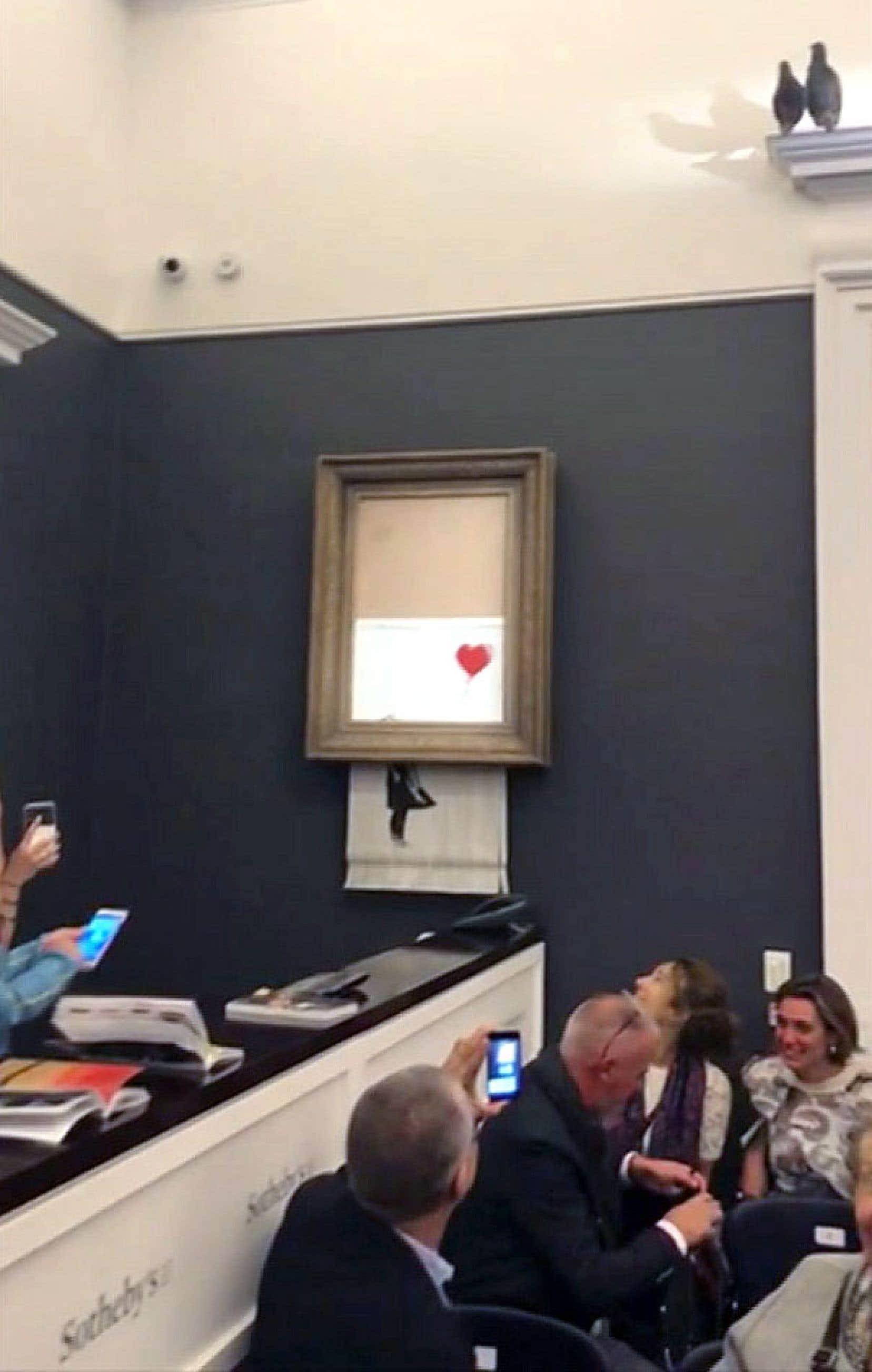 Sitôt <em>La petite fille au ballon rouge</em> adjugée, l'œuvre de Banksy a glissé hors de son gros cadre pour être à moitié réduite en bandelettes par une déchiqueteuse dissimulée.