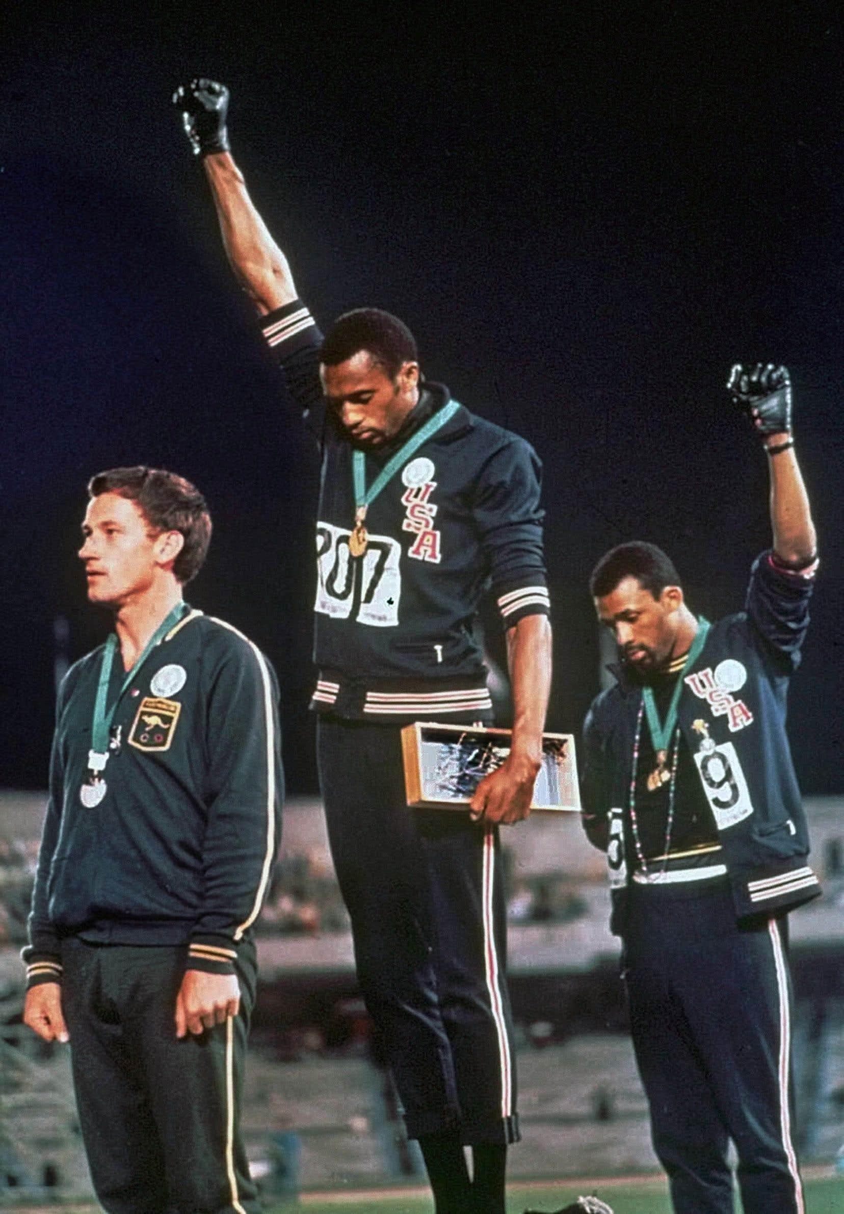 Les poings gantés de noir de Tommie Smith (au centre) et de John Carlos (à droite) levés vers le ciel de Mexico, leurs têtes baissées, onttotalement redéfini le concept de militantisme dans le sport.