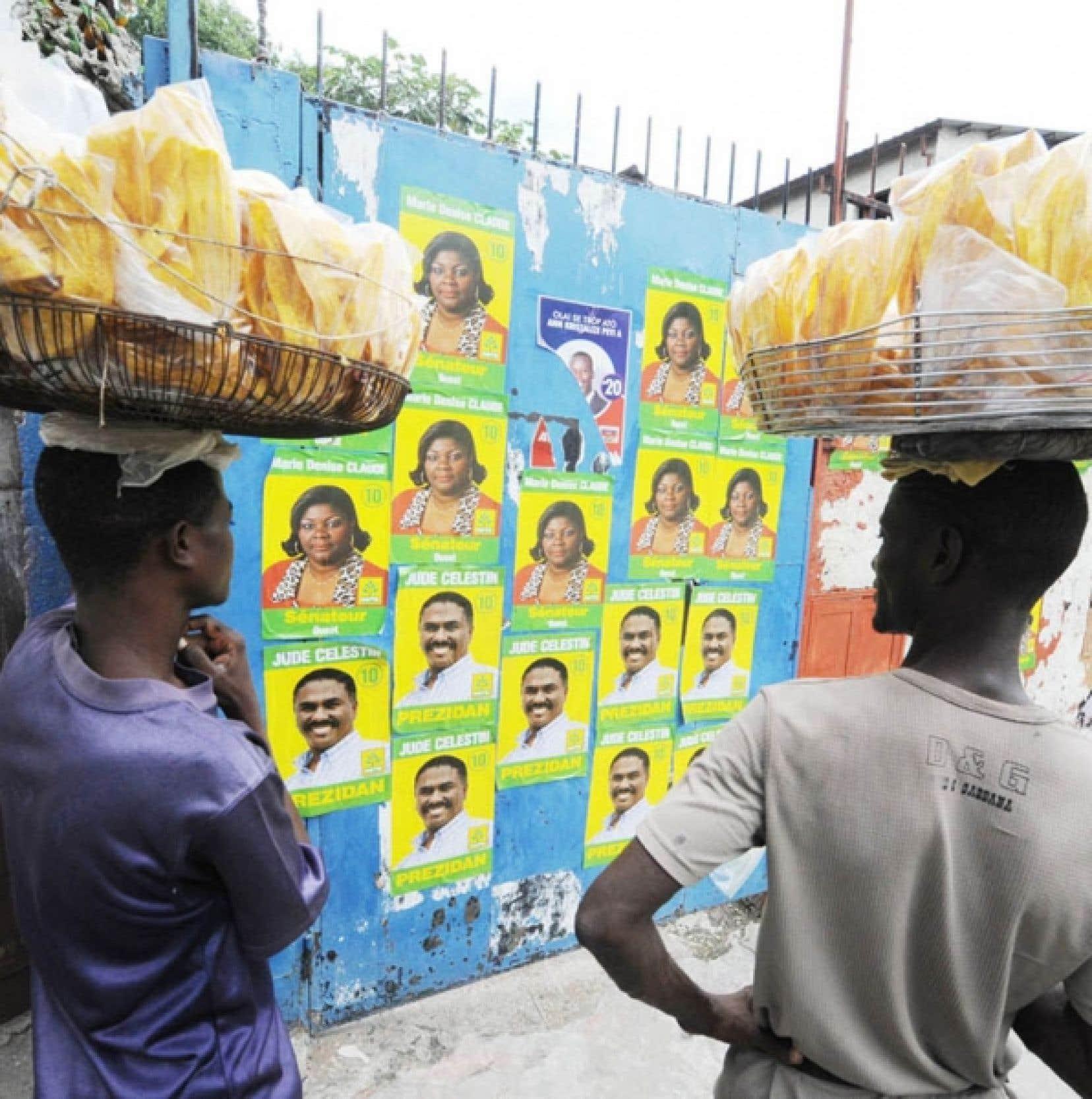 Marchands ambulants devant des affiches électorales à Port-au-Prince<br />