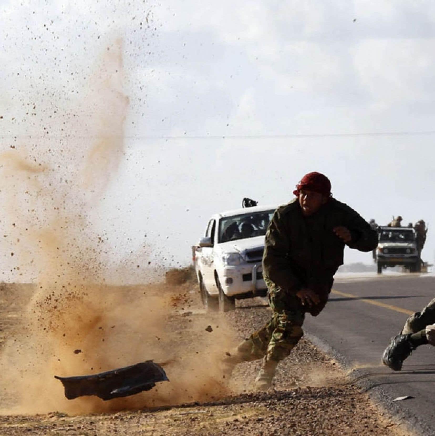 Des rebelles libyens tentent d'éviter les tirs de l'artillerie gouvernementale sur la route de Bin Djaouad, ville côtière à 160 km à l'est de Syrte, fief convoité de Mouammar Kadhafi. Les rebelles avaient pris le contrôle de Bin Djaouad samedi, mais ont été repoussés hier.<br />