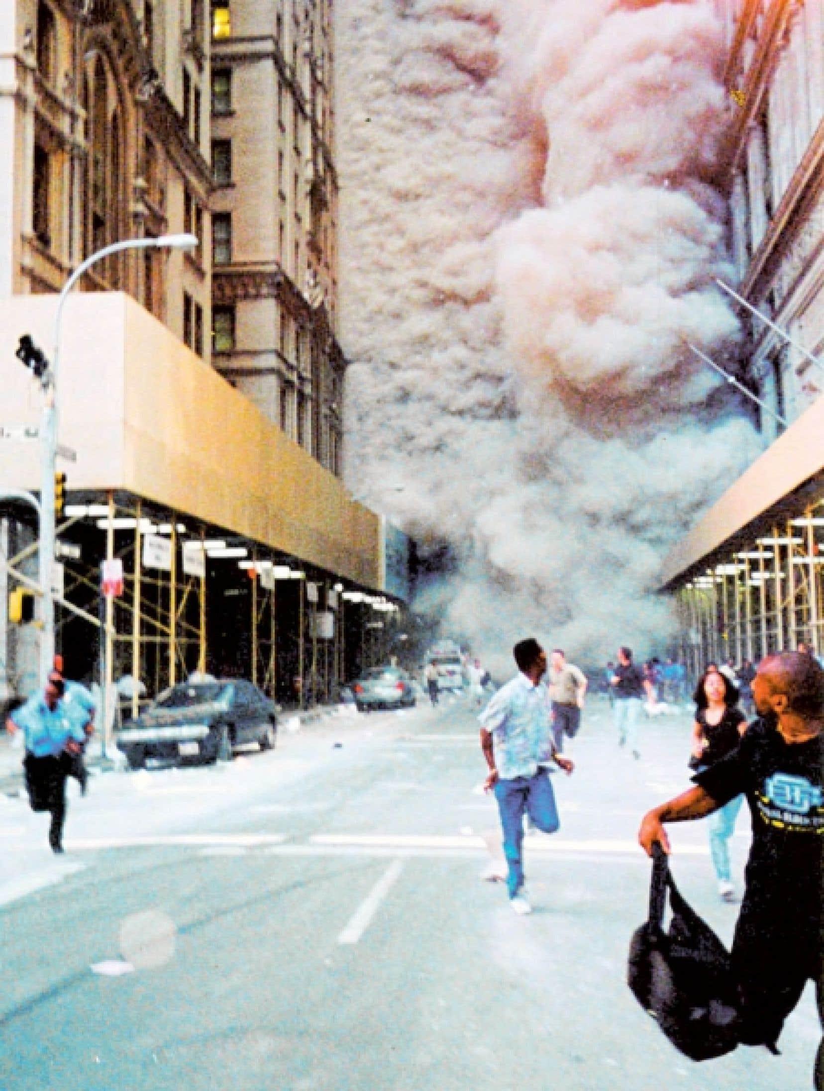 Après l'effondrement du World Trade Center, des New-Yorkais se sauvent du nuage de poussière qui s'engouffre rue Broadway.<br />