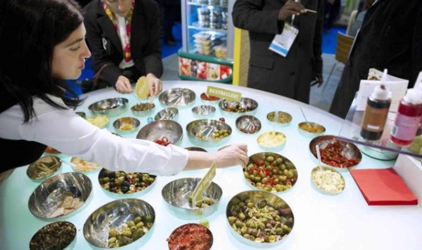 Une femme déguste des olives pendant le Salon international de l'alimentation de Paris. L'édition du SIAL de Montréal a lieu du 9 au 11 mai.