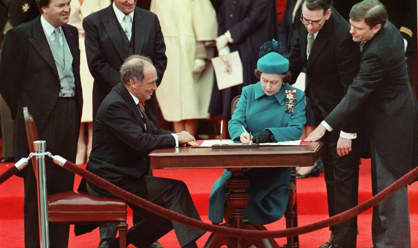 Sous le regard attentif du premier ministre Pierre Elliott Trudeau, la reine Elizabeth signe la proclamation de la Loi constitutionnelle du Canada à Ottawa, le 17 avril 1982.