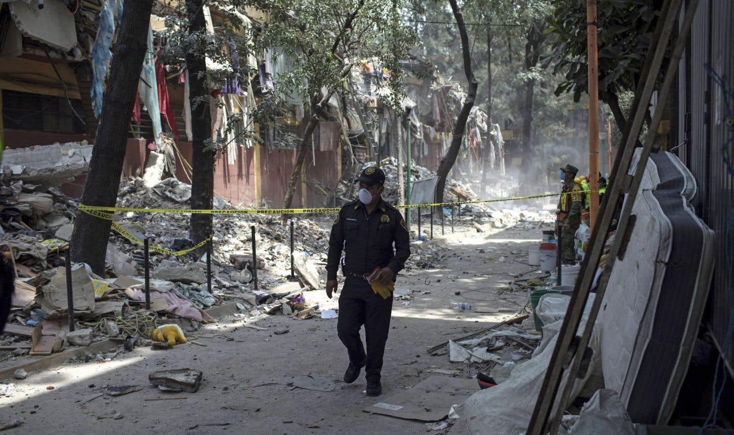 Un policier en quête de survivants marche dans une rue où s'amoncellent les débris à Mexico.