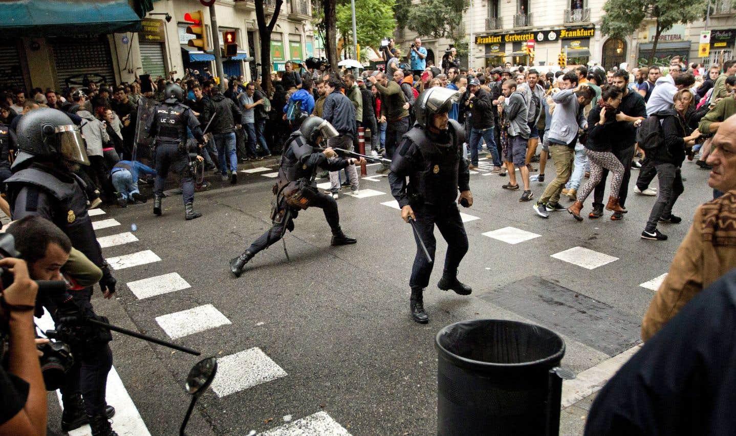 Des policiers antiémeutes repoussent des gens qui essaient d'entrer dans un bureau de scrutin de Barcelone pour participer au référendum.