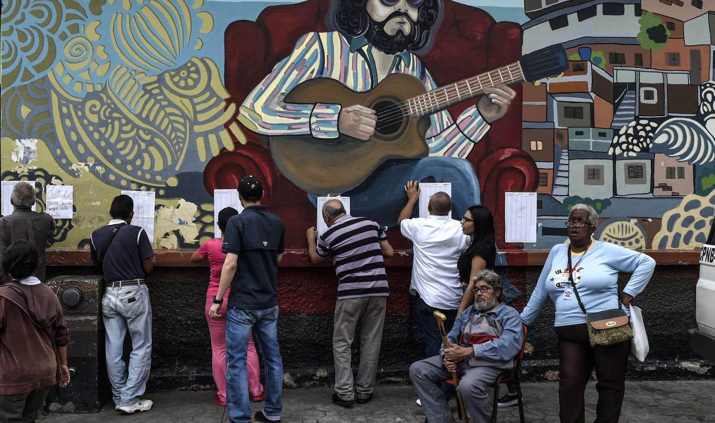 Des Vénézuéliens examinent des listes électorales pour y retrouver leur nom avant de voter, à Caracas, dimanche.