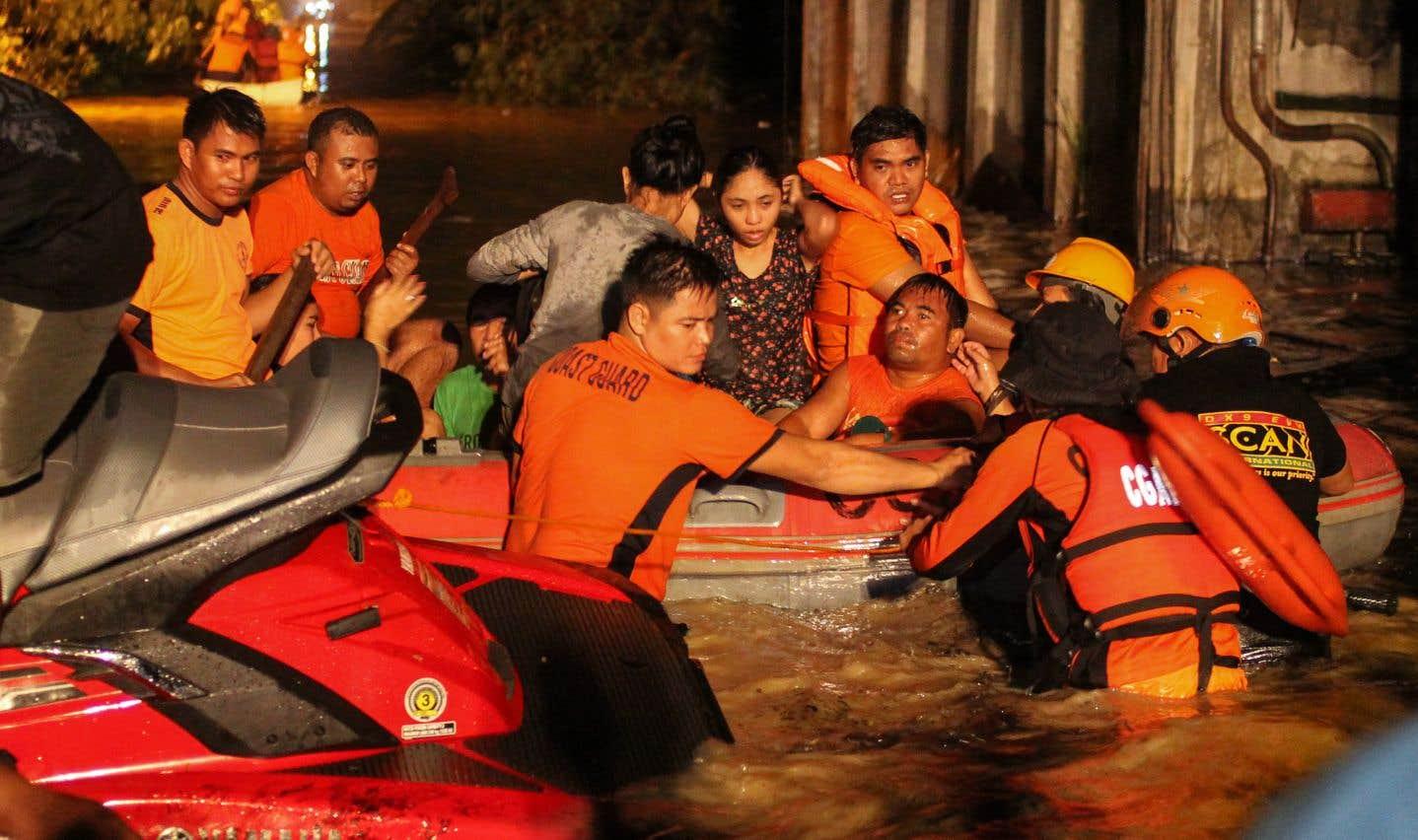 Des secouristes évacuent les résidents touchés par les inondations à Davao, sur l'île de Mindanao, dans le sud des Philippines, samedi.