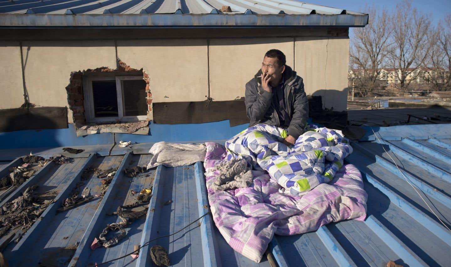 Un travailleur migrant se repose sur le toit de la maison dont il a été évincé dans un village des environs de Pékin.