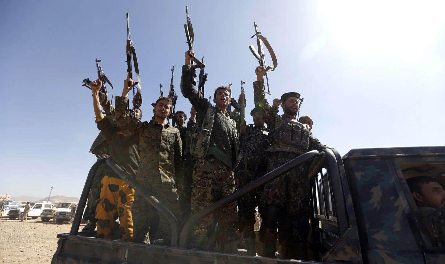 Des combattants houthis nouvellement recrutés scandent des slogans alors qu'ils montent un véhicule militaire lors d'un rassemblement dans la capitale Sanaa, le 3 janvier dernier.