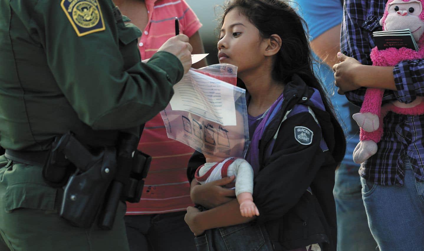 La petite Stefany Marjorie, âgée de 8ans, regarde un agent des douanes américaines vérifier les informations de sa famille à leur arrivée à Mission, au Texas.
