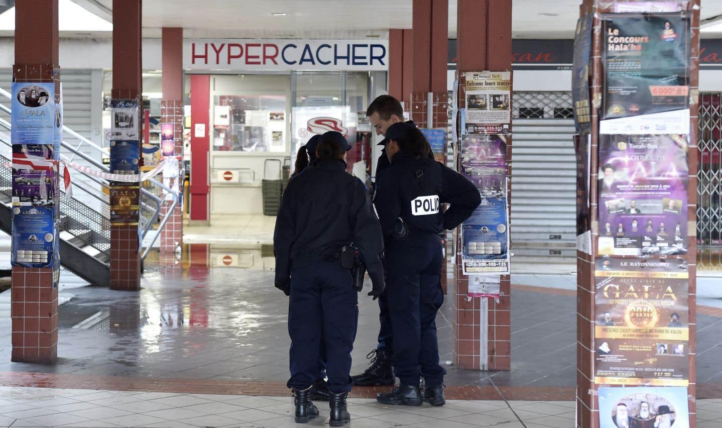 Des policiers français se tiennent devant une épicerie casher française mardi à Creteil, au sud de Paris. L'établissement a été détruit par un incendie criminel qui a ravivé les craintes d'antisémitisme.