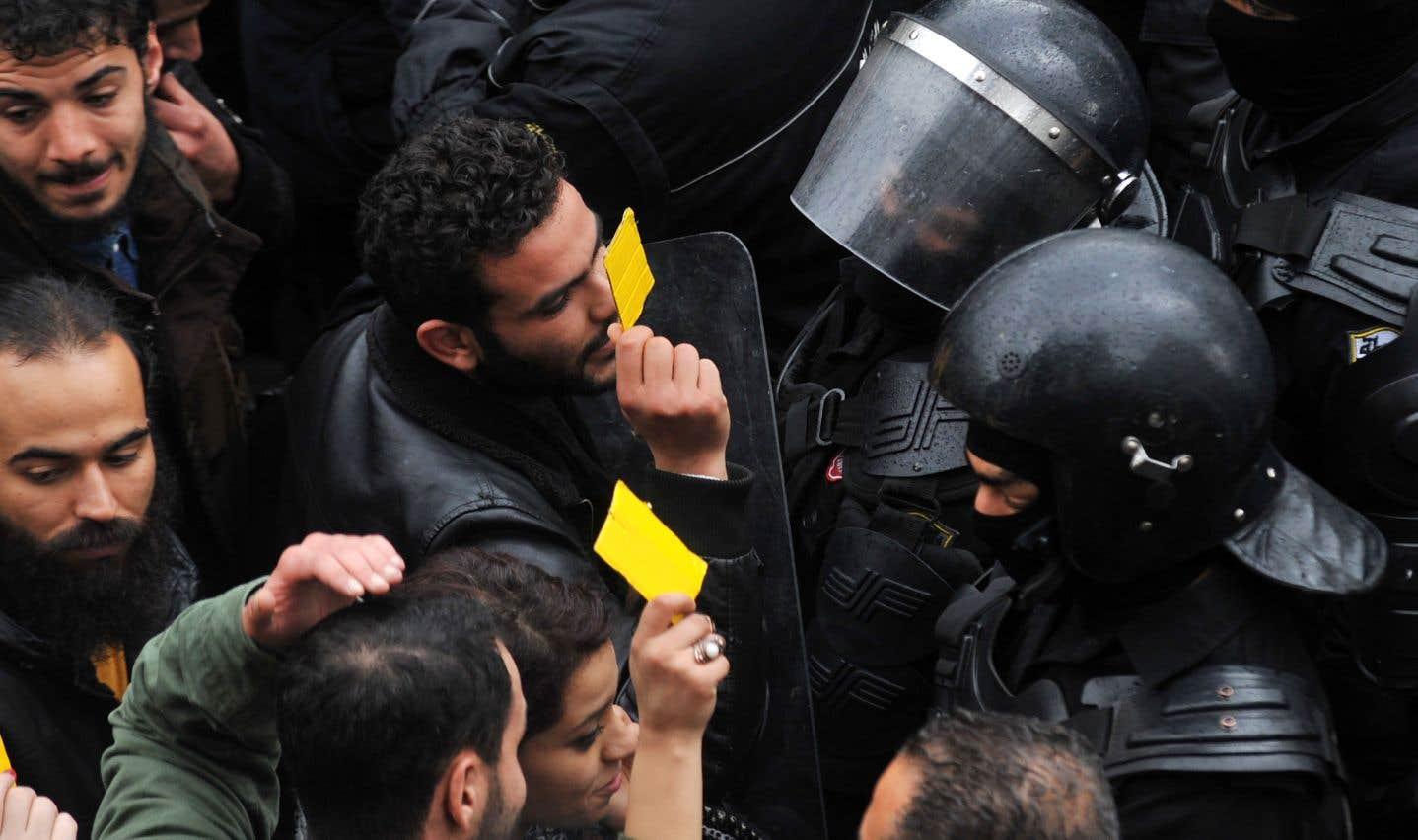 Des manifestants tunisiens confrontent des policiers qui leur bloquent l'accès aux bureaux du gouvernement, à Tunis, le 12 janvier.
