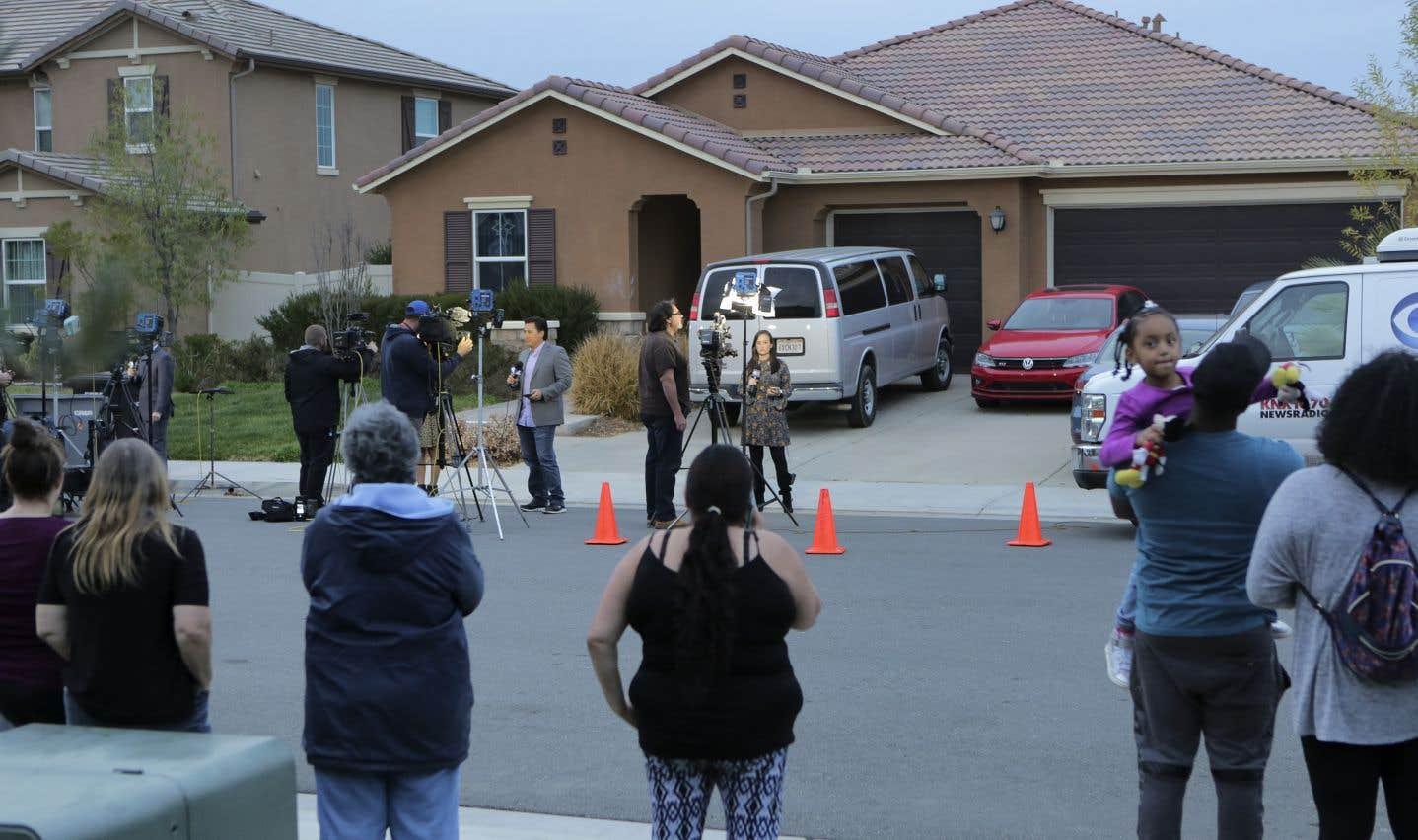 Des résidants de Perris sont rassemblés avec des représentants des médias devant la maison où les autorités ont trouvé les douze enfants retenus captifs.
