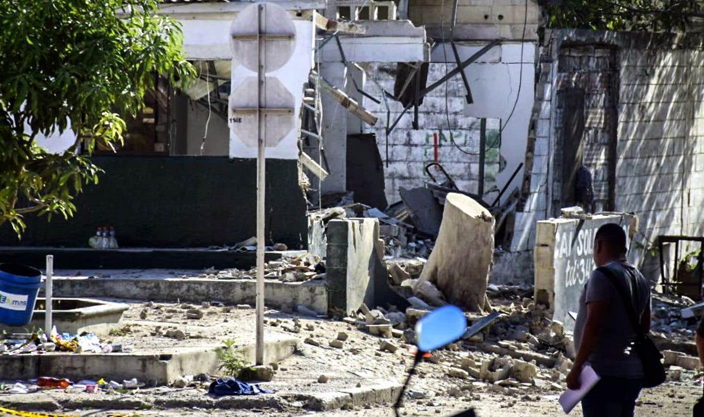 Un homme passe devant un poste de police après un attentat à la bombe dans le département de Soledad Atlantico, en Colombie, dimanche.