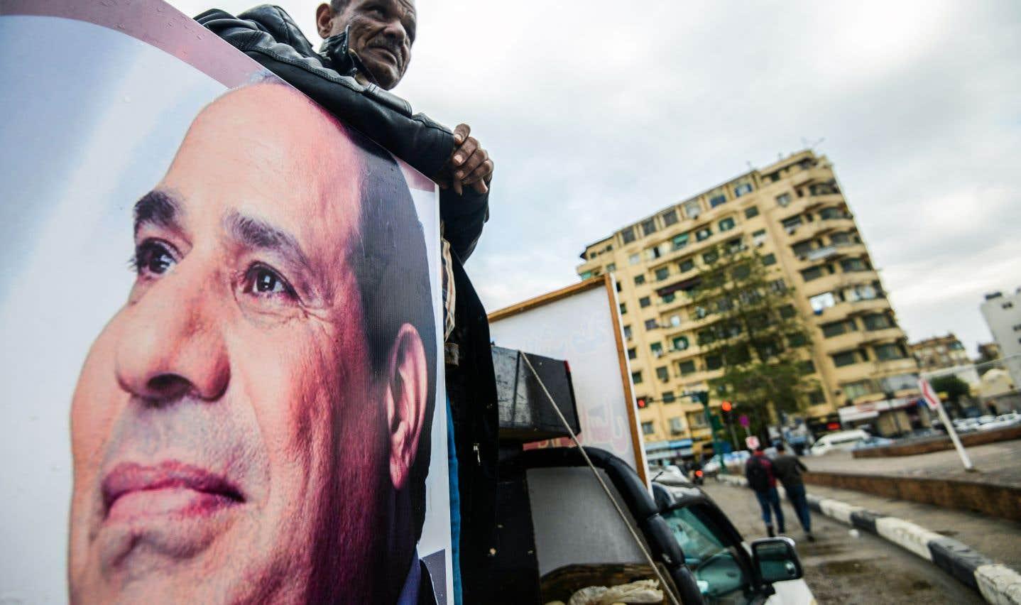 Un sympathisant du président Abdel Fattah al-Sisi se tient à l'arrière d'une camionnette portant son portrait sur la place Tahrir de la capitale, jeudi dernier.