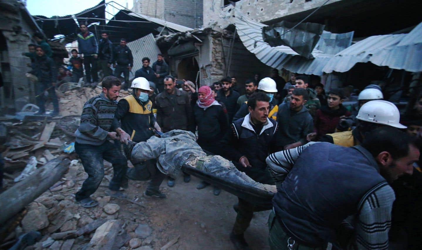 Les membres des forces de défense civile syriennes connues sous le nom de Casques blancs évacuent une victime à la suite de raids aériens à Arbine, dans la Ghouta orientale, vendredi.