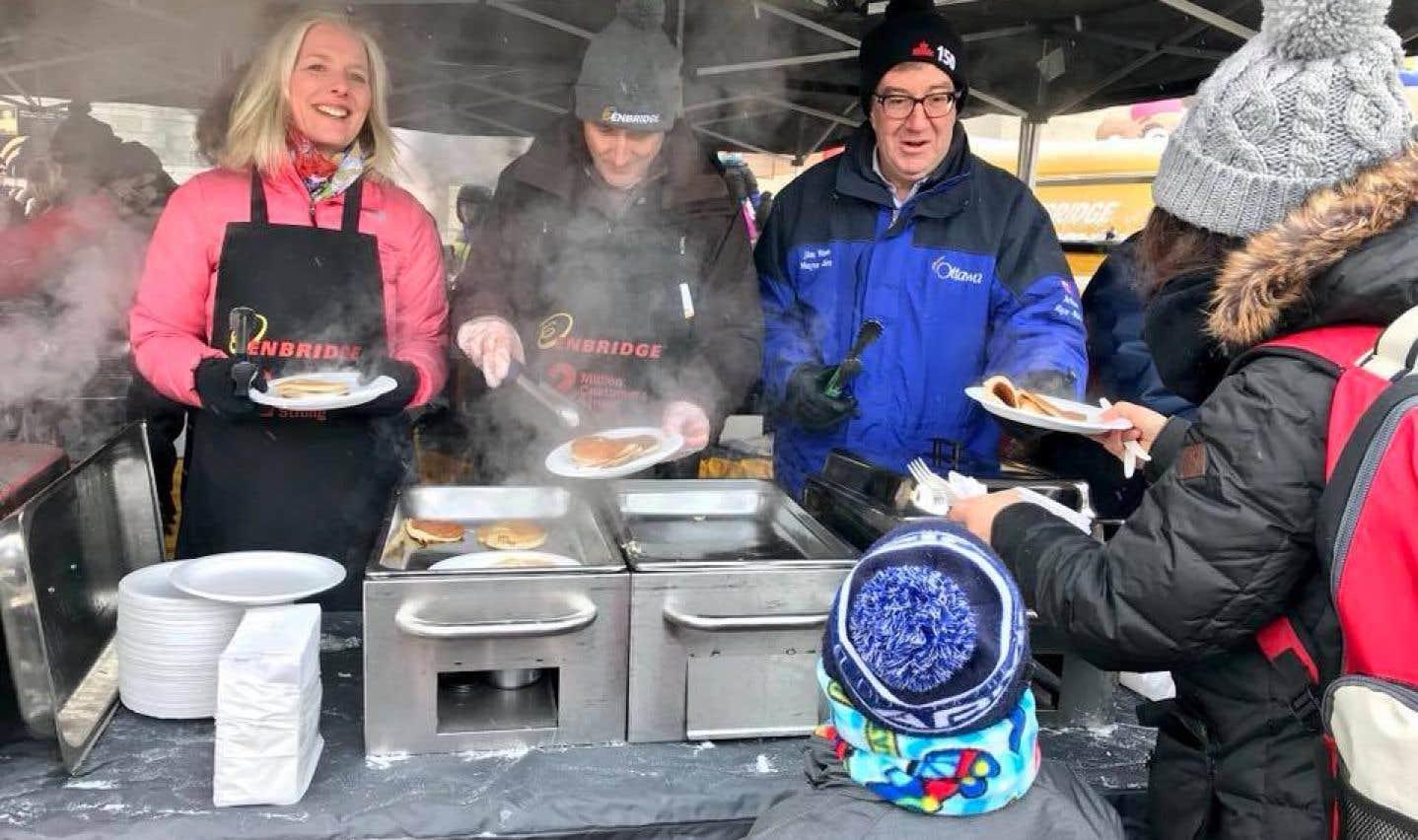 La ministre fédérale de l'Environnement, Catherine McKenna, en compagnie de Jim Sanders, président d'Enbridge Gas Distribution (au centre), lors dudéjeuner annuel Enbridge du Bal de neige d'Ottawa, au début février