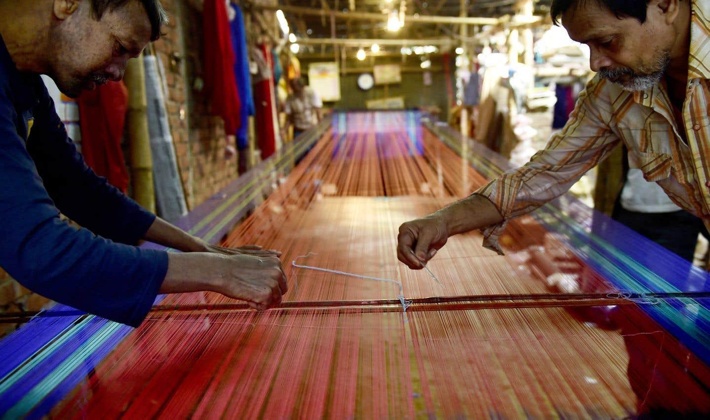 Des tisserands bangladais travaillent à l'intérieur d'une usine de tissage à la main à Dacca.