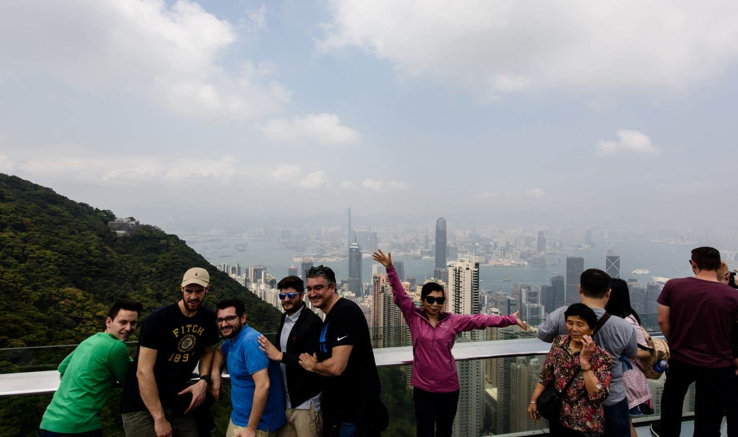 Des touristes photographiés au sommet du Pic Victoria, qui offre une vue imprenable sur la ville de Hong Kong