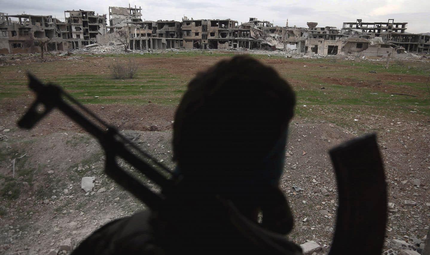 Un combattant du groupe rebelle Faylaq al-Rahmane regarde des bâtiments endommagés sur la ligne de front dans la Ghouta orientale, près de Damas.