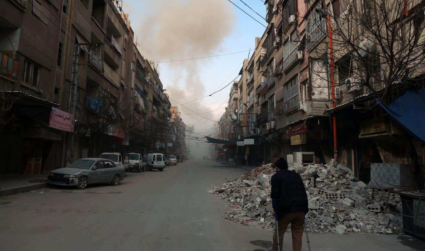 Un membre des Casques blancs sonde le site d'une frappe aérienne du régime syrien, vendredi, dans la ville rebelle de Saqba.