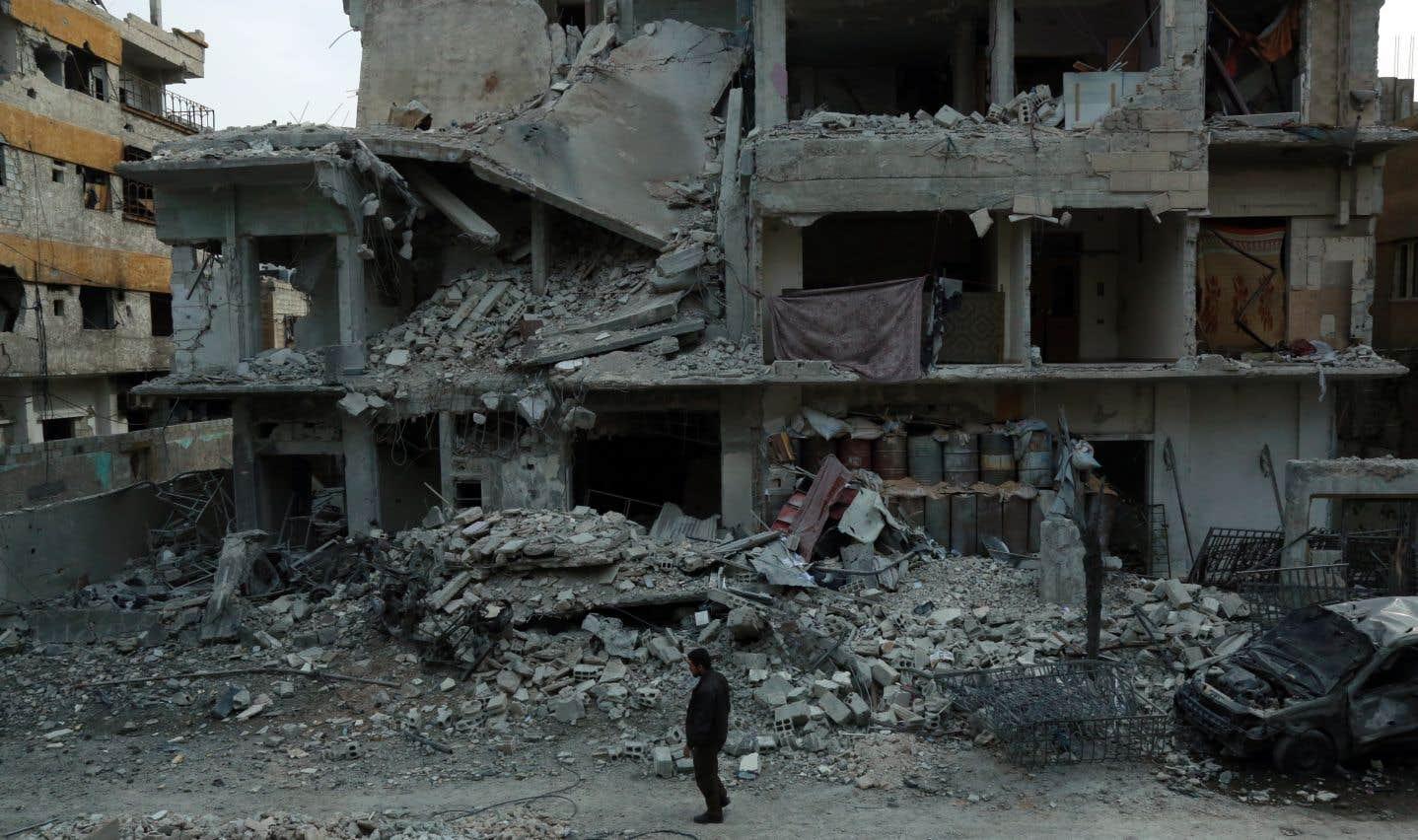 Un homme marche parmi les décombres dans la ville rebelle de Douma, faisant partie de la région assiégée de la Ghouta orientale.
