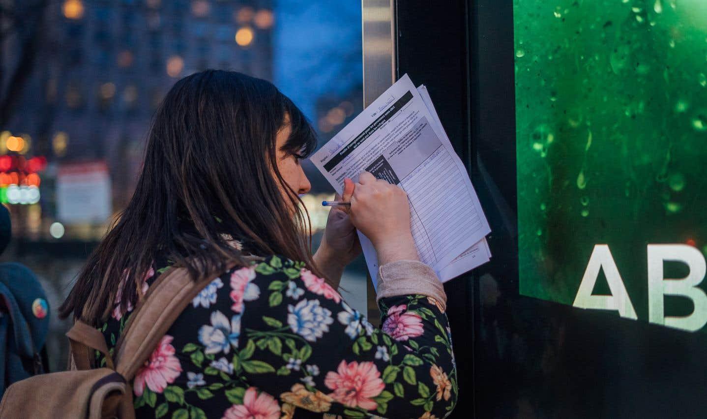 Megan Cacchiotti, une bénévole, prend des notes à la place Émlie-Gamelin.