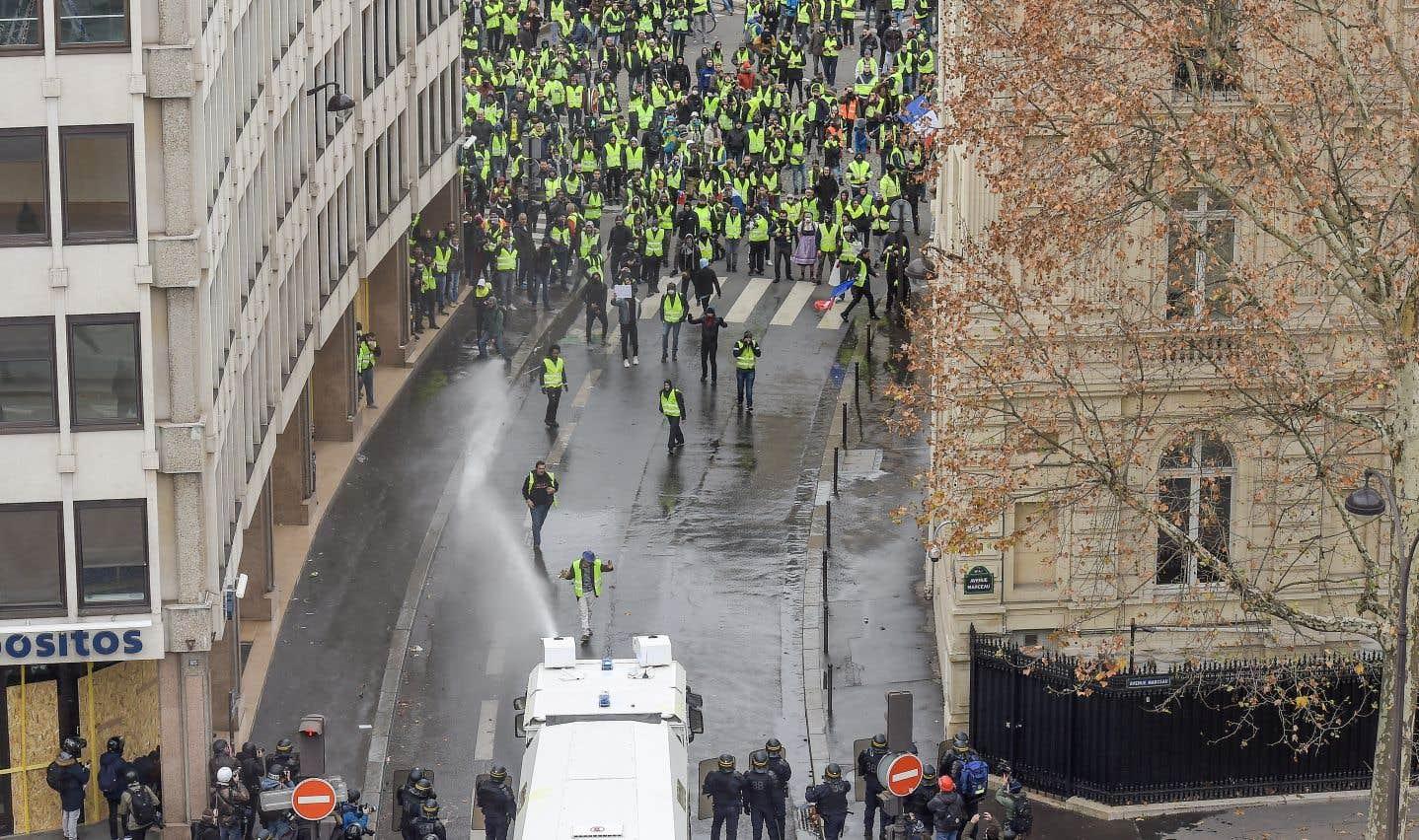 Des policiers tentent de disperser des manifestants à l'aide d'un canon à eau, près de l'Arc de Triomphe, à Paris.