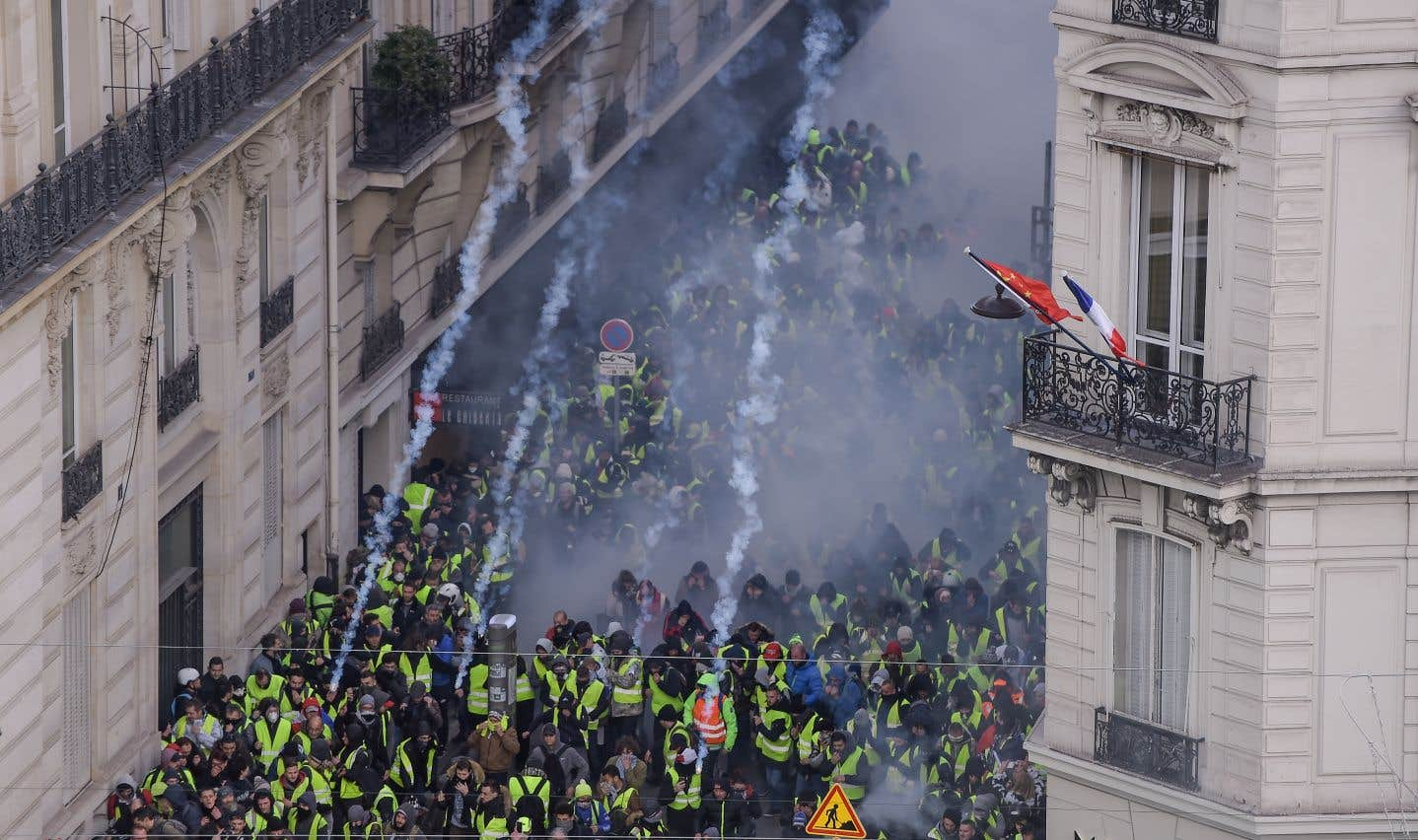 Un groupe de manifestants et des policiers anti-émeutes s'affrontent au milieu de gaz lacrymogènes sur les Champs-Élysées, à Paris.