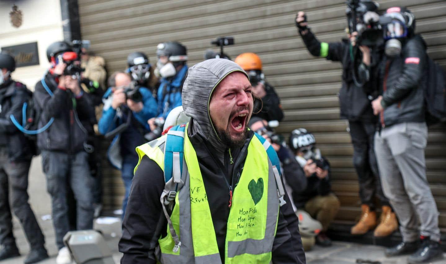 Un manifestant fait face aux policiers anti-émeute près de l'avenue des Champs-Élysées, à Paris.